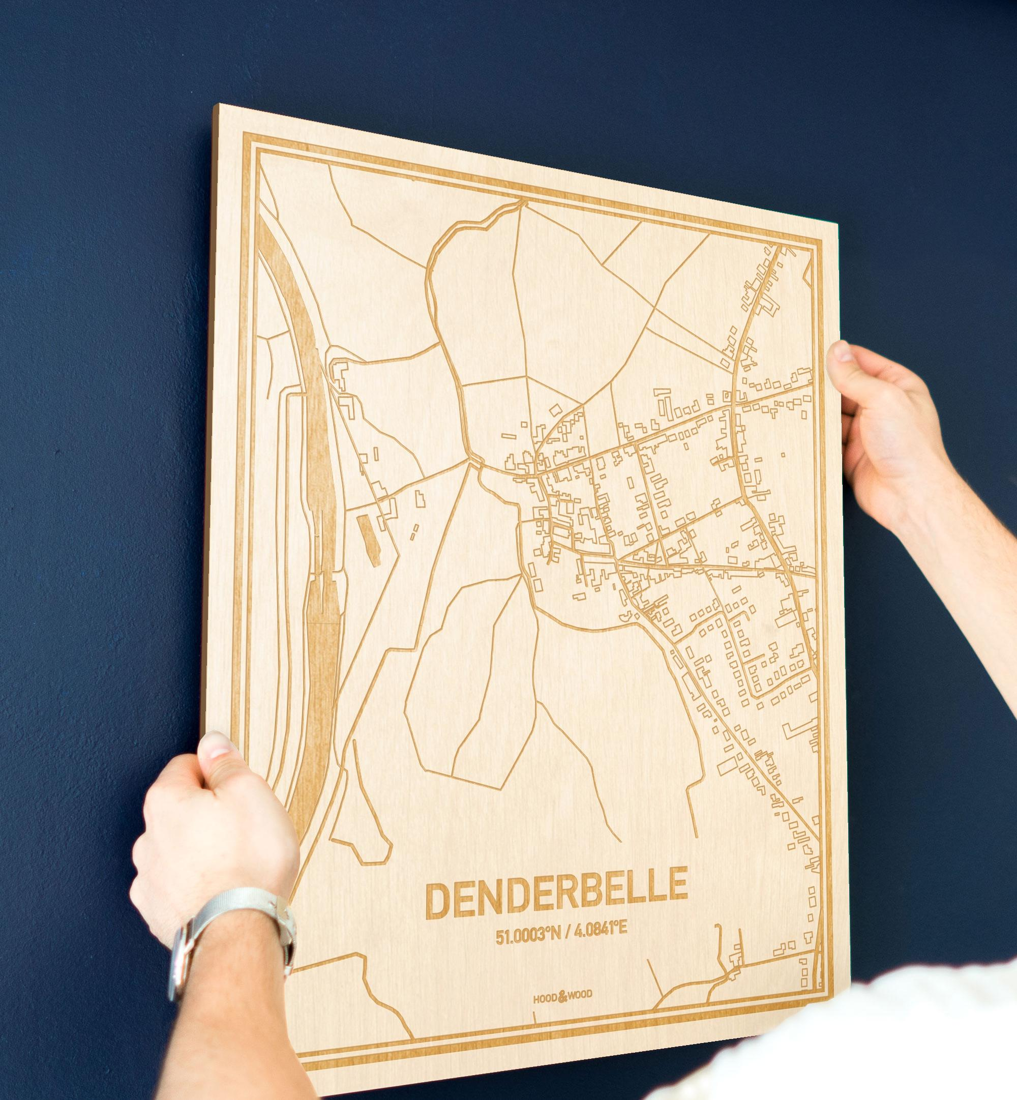 Een man hangt de houten plattegrond Denderbelle aan zijn blauwe muur ter decoratie. Je ziet alleen zijn handen de kaart van deze unieke in Oost-Vlaanderen  vasthouden.