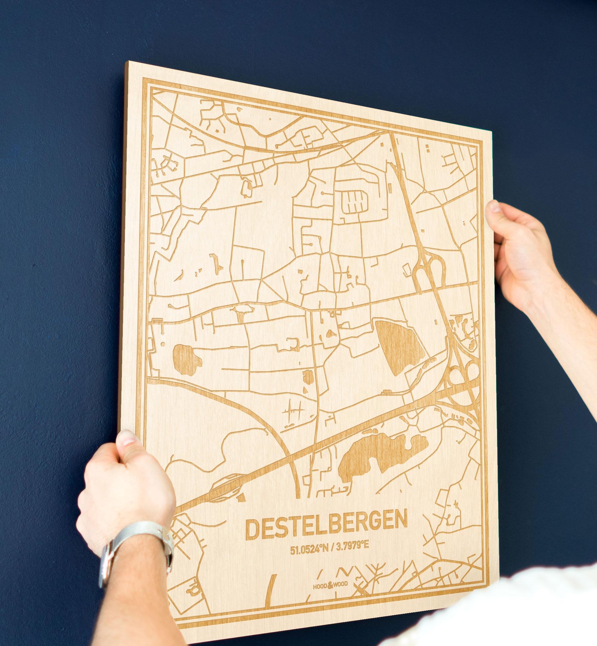 Een man hangt de houten plattegrond Destelbergen aan zijn blauwe muur ter decoratie. Je ziet alleen zijn handen de kaart van deze speciale in Oost-Vlaanderen  vasthouden.