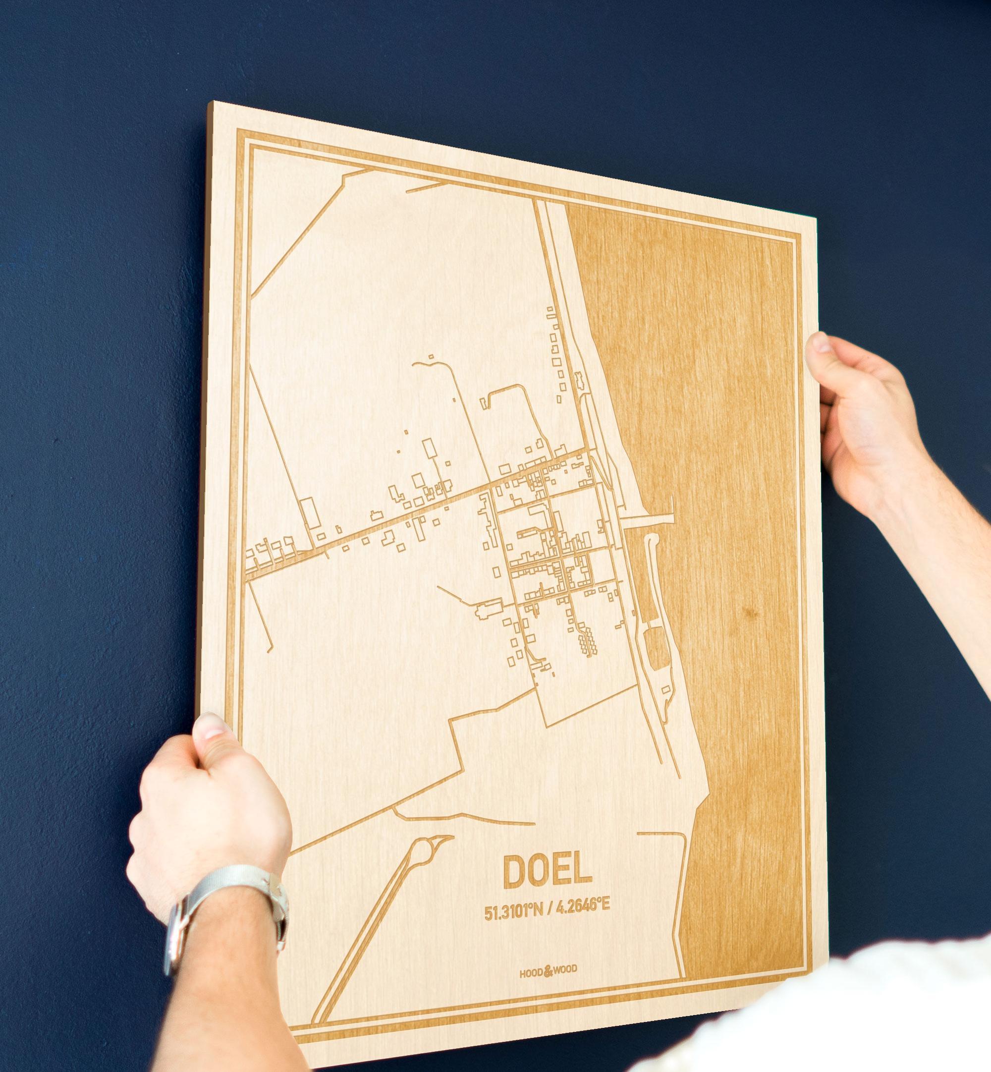 Een man hangt de houten plattegrond Doel aan zijn blauwe muur ter decoratie. Je ziet alleen zijn handen de kaart van deze unieke in Oost-Vlaanderen  vasthouden.