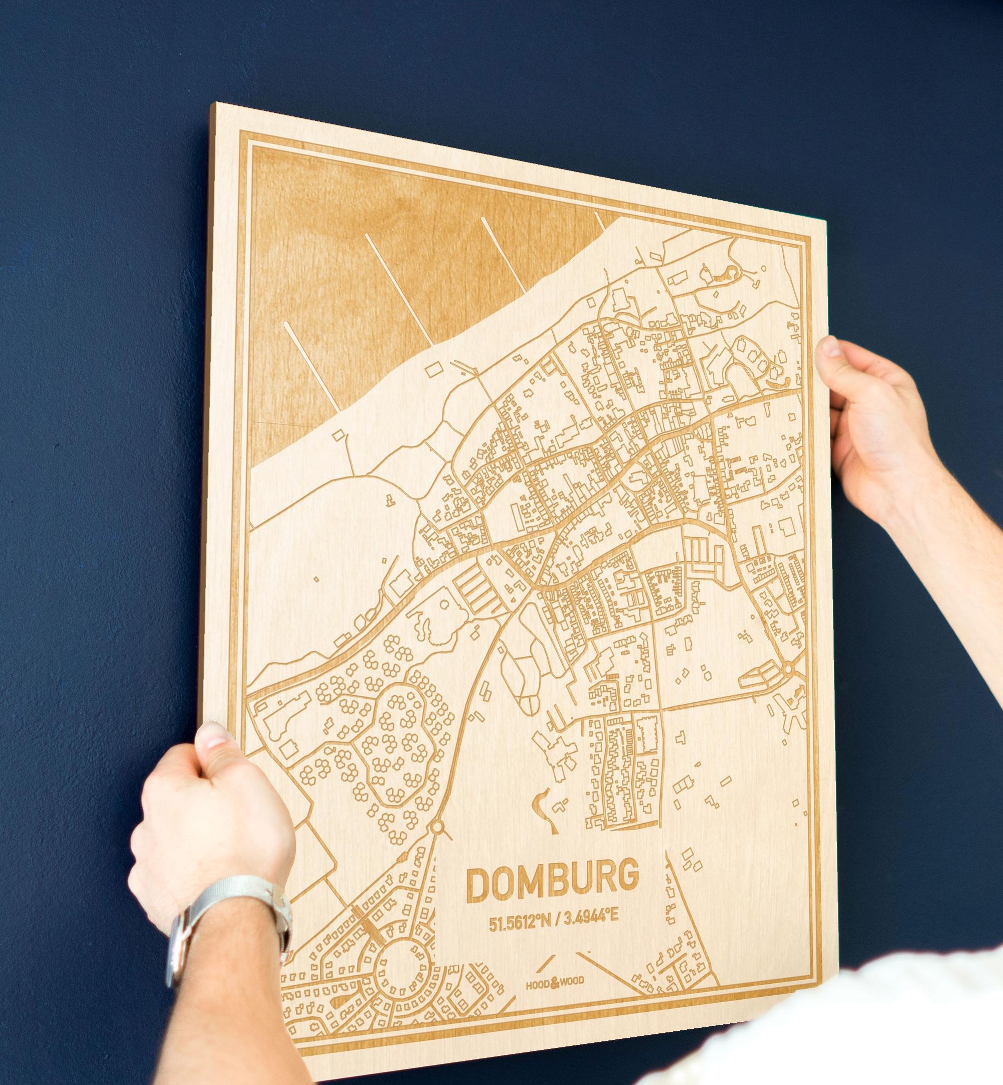Een man hangt de houten plattegrond Domburg aan zijn blauwe muur ter decoratie. Je ziet alleen zijn handen de kaart van deze speciale in Zeeland vasthouden.