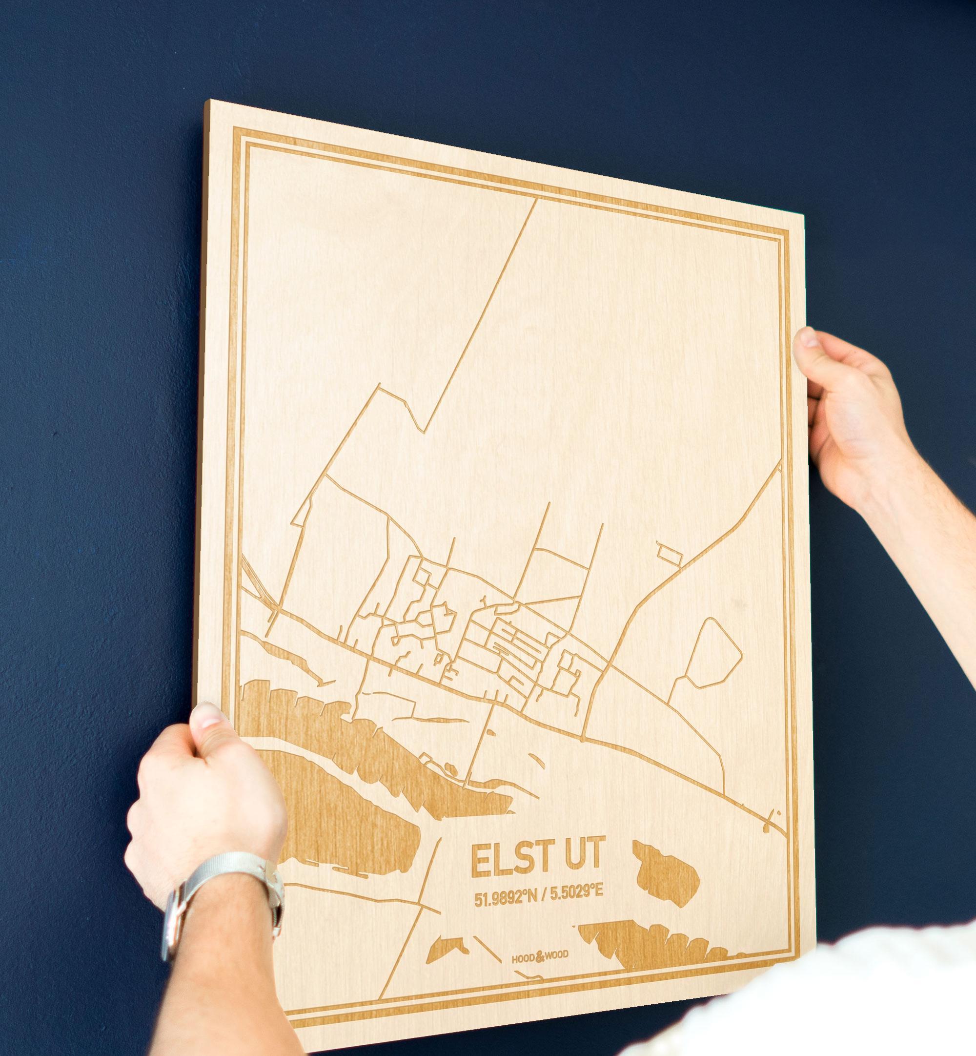 Een man hangt de houten plattegrond Elst Ut aan zijn blauwe muur ter decoratie. Je ziet alleen zijn handen de kaart van deze verrassende in Utrecht vasthouden.