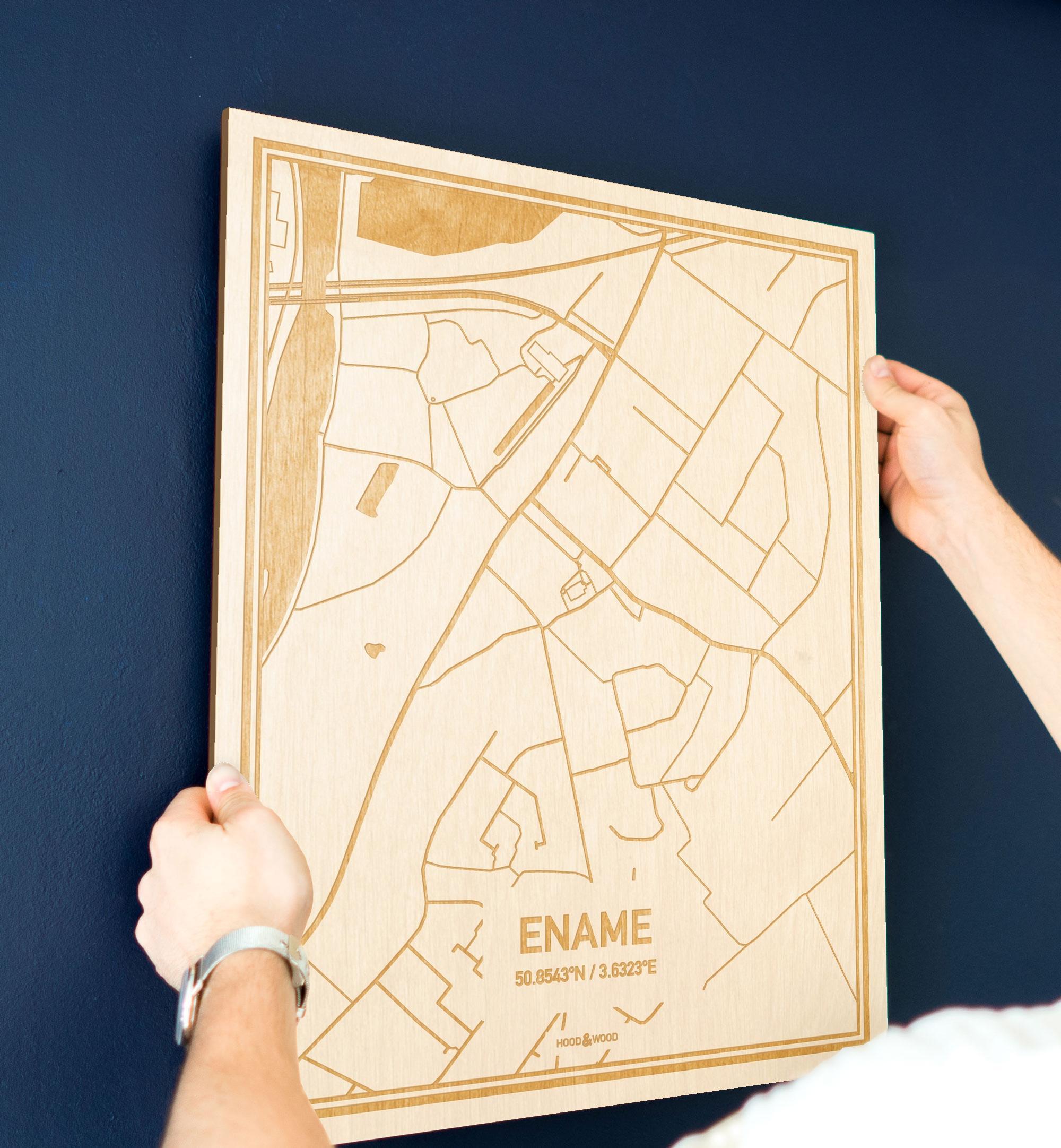 Een man hangt de houten plattegrond Ename aan zijn blauwe muur ter decoratie. Je ziet alleen zijn handen de kaart van deze verrassende in Oost-Vlaanderen  vasthouden.