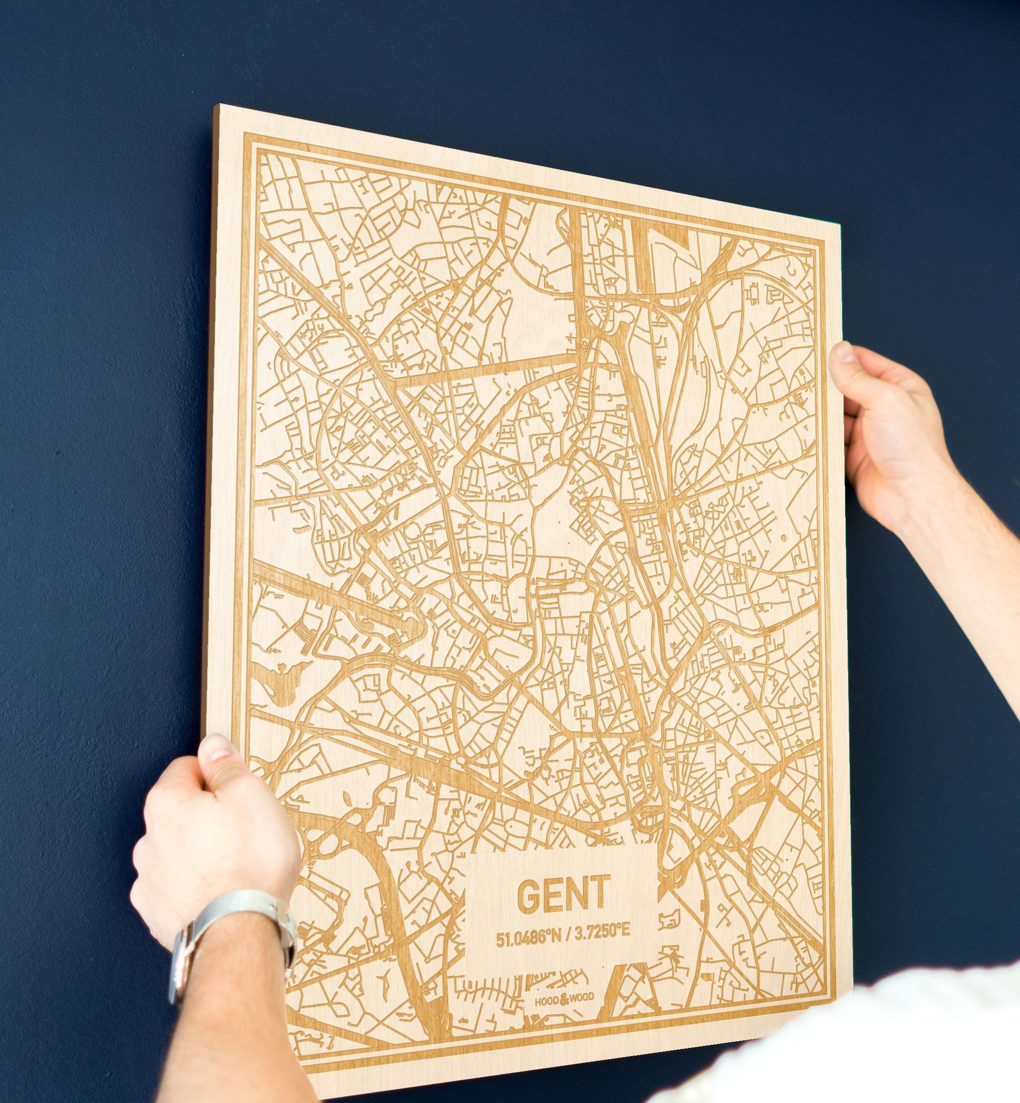 Een man hangt de houten plattegrond Gent aan zijn blauwe muur ter decoratie. Je ziet alleen zijn handen de kaart van deze opvallende in Oost-Vlaanderen  vasthouden.