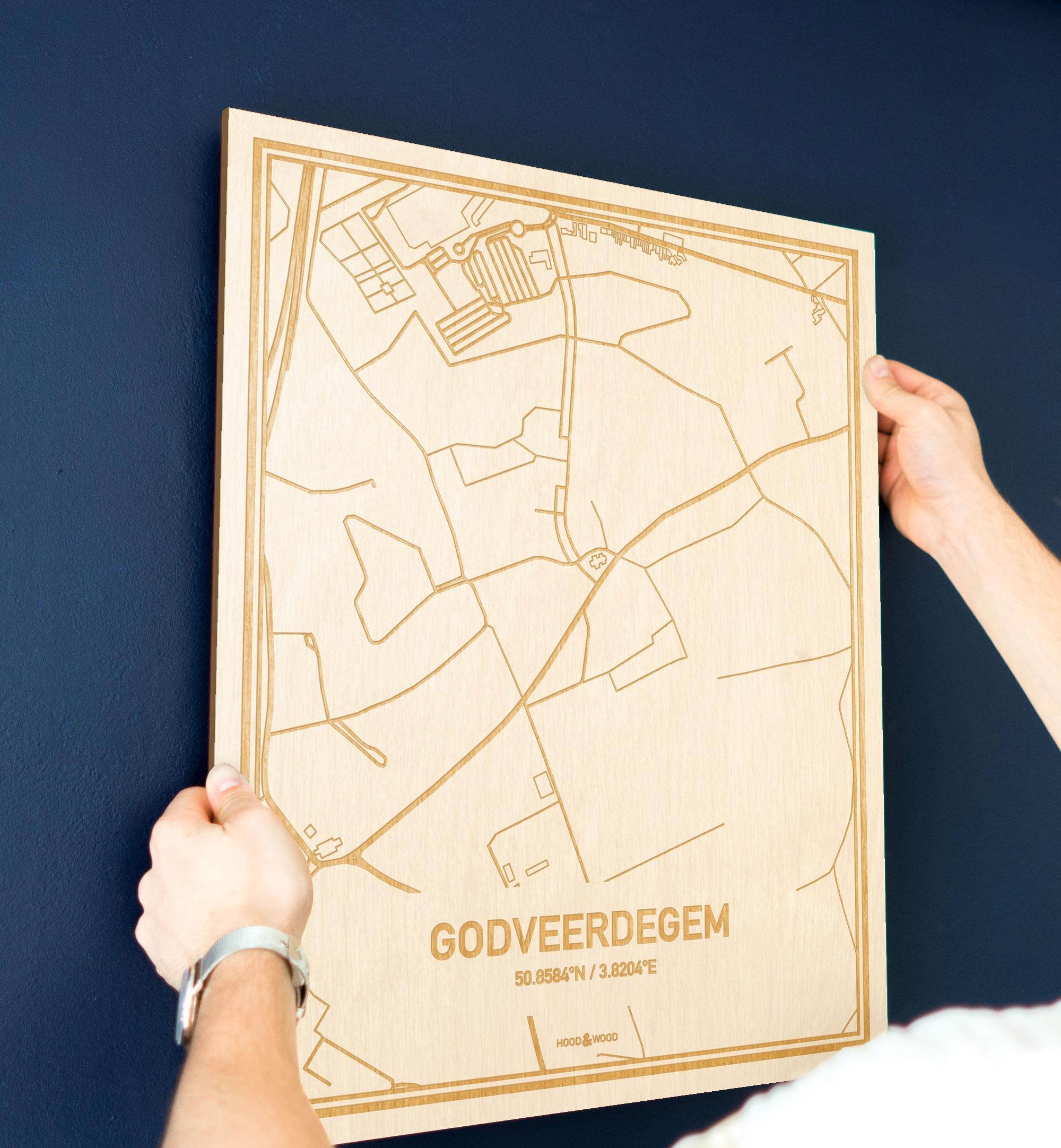 Een man hangt de houten plattegrond Godveerdegem aan zijn blauwe muur ter decoratie. Je ziet alleen zijn handen de kaart van deze bijzondere in Oost-Vlaanderen  vasthouden.