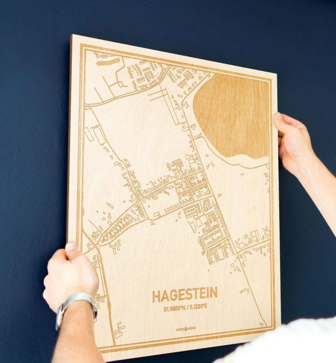 Een man hangt de houten plattegrond Hagestein aan zijn blauwe muur ter decoratie. Je ziet alleen zijn handen de kaart van deze moderne in Utrecht vasthouden.