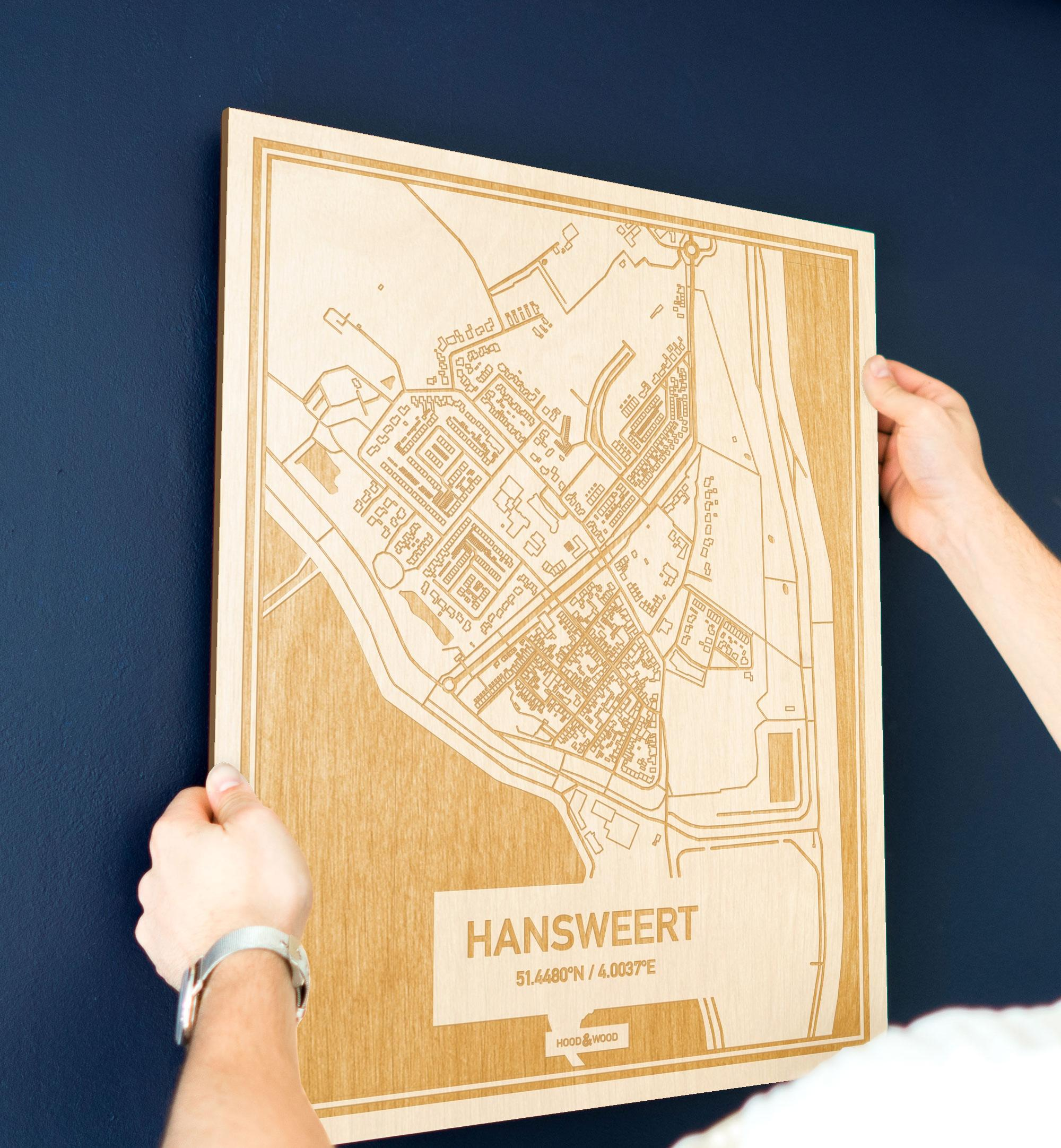 Een man hangt de houten plattegrond Hansweert aan zijn blauwe muur ter decoratie. Je ziet alleen zijn handen de kaart van deze speciale in Zeeland vasthouden.