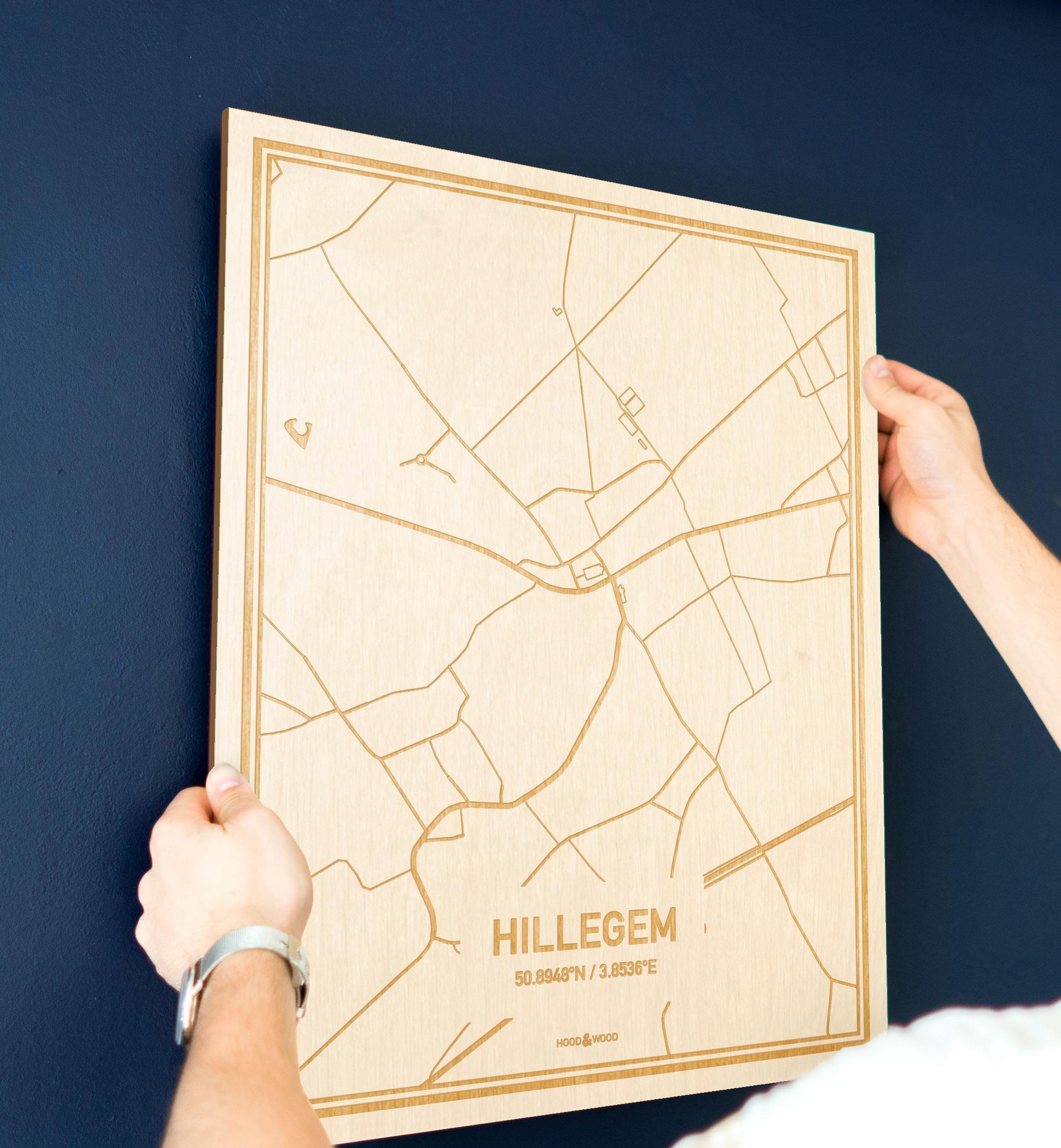 Een man hangt de houten plattegrond Hillegem aan zijn blauwe muur ter decoratie. Je ziet alleen zijn handen de kaart van deze schitterende in Oost-Vlaanderen  vasthouden.