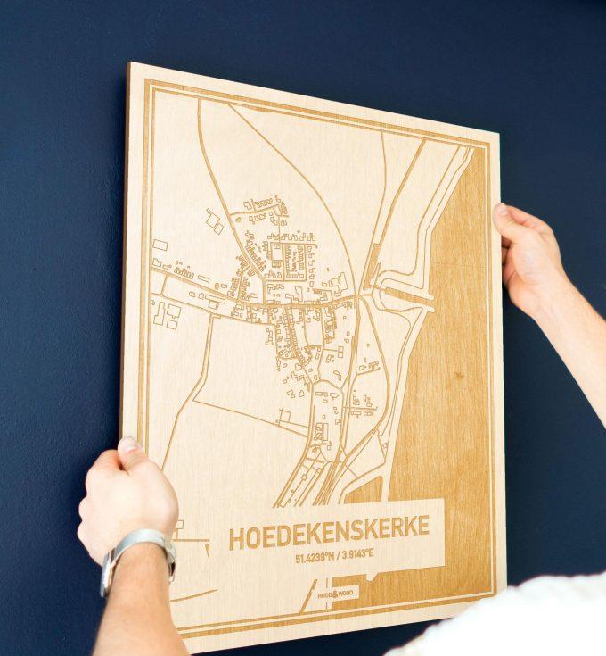 Een man hangt de houten plattegrond Hoedekenskerke aan zijn blauwe muur ter decoratie. Je ziet alleen zijn handen de kaart van deze unieke in Zeeland vasthouden.