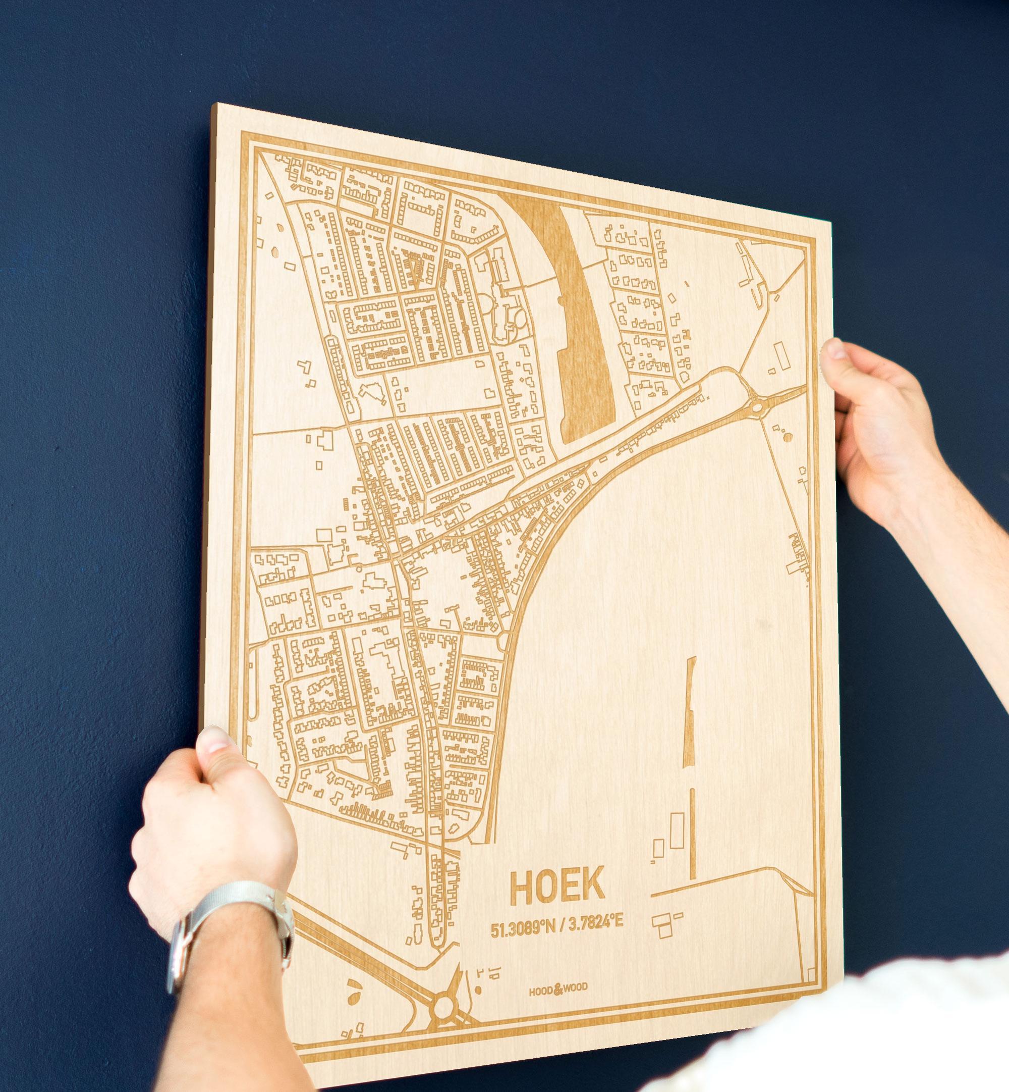 Een man hangt de houten plattegrond Hoek aan zijn blauwe muur ter decoratie. Je ziet alleen zijn handen de kaart van deze originele in Zeeland vasthouden.