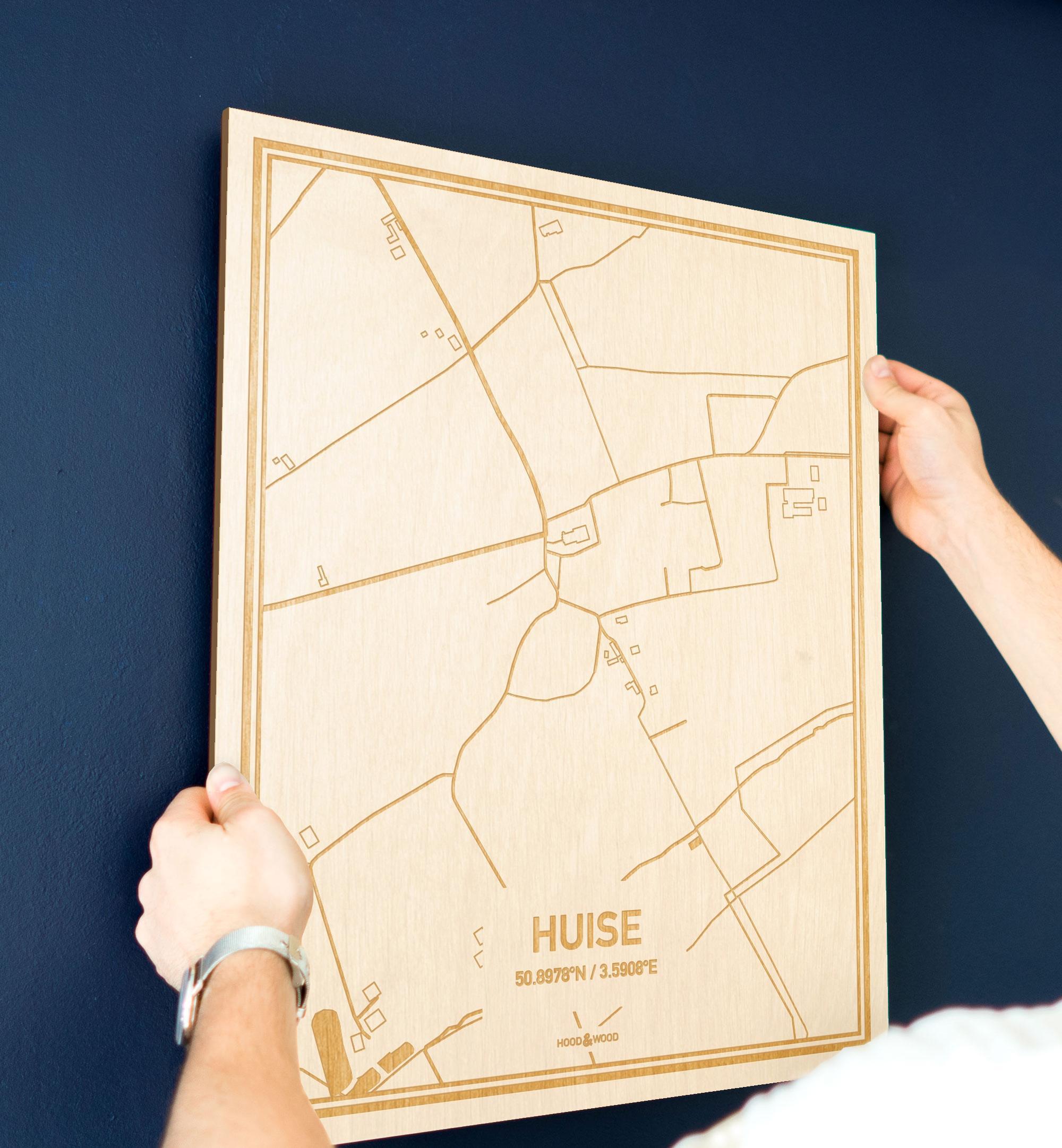 Een man hangt de houten plattegrond Huise aan zijn blauwe muur ter decoratie. Je ziet alleen zijn handen de kaart van deze moderne in Oost-Vlaanderen  vasthouden.