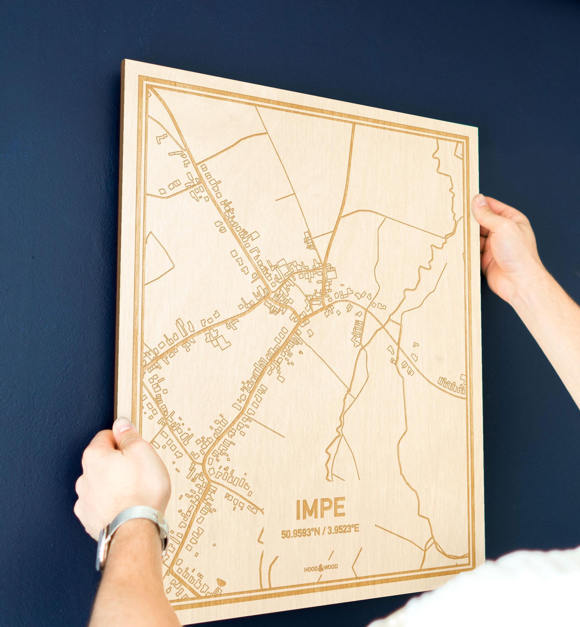 Een man hangt de houten plattegrond Impe aan zijn blauwe muur ter decoratie. Je ziet alleen zijn handen de kaart van deze unieke in Oost-Vlaanderen  vasthouden.