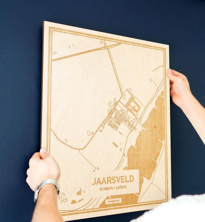 Een man hangt de houten plattegrond Jaarsveld aan zijn blauwe muur ter decoratie. Je ziet alleen zijn handen de kaart van deze stijlvolle in Utrecht vasthouden.