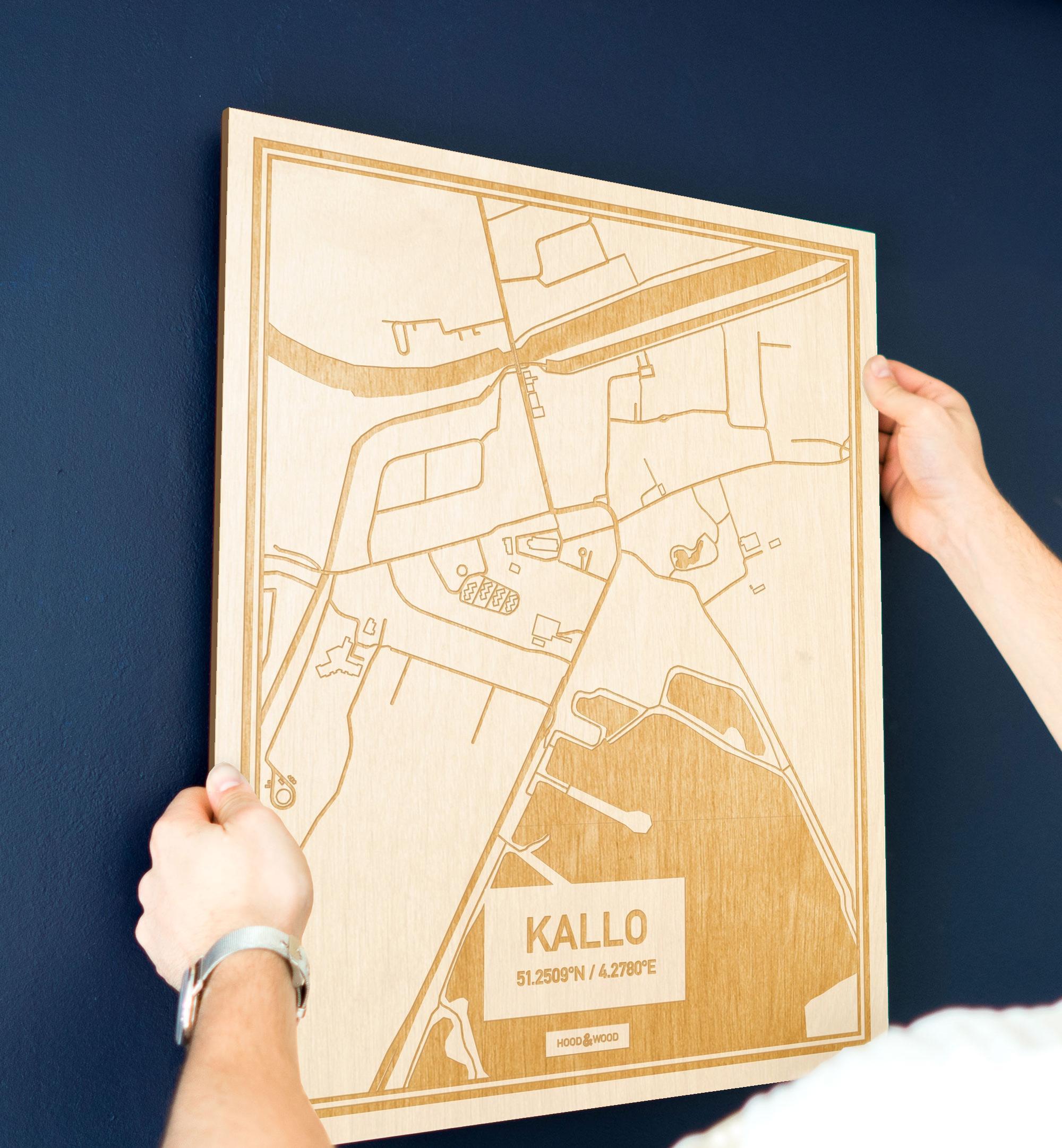 Een man hangt de houten plattegrond Kallo aan zijn blauwe muur ter decoratie. Je ziet alleen zijn handen de kaart van deze stijlvolle in Oost-Vlaanderen  vasthouden.