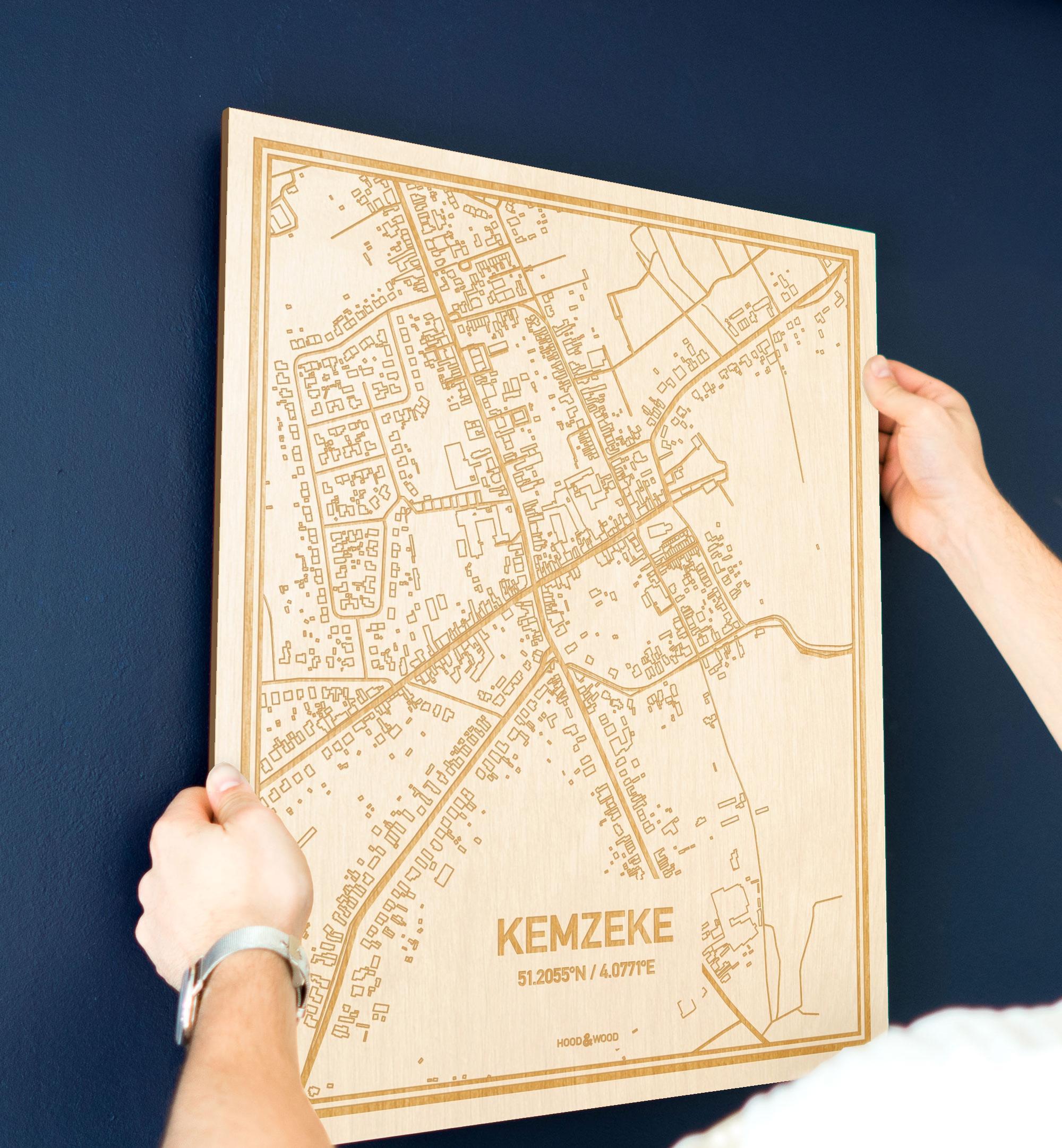 Een man hangt de houten plattegrond Kemzeke aan zijn blauwe muur ter decoratie. Je ziet alleen zijn handen de kaart van deze stijlvolle in Oost-Vlaanderen  vasthouden.