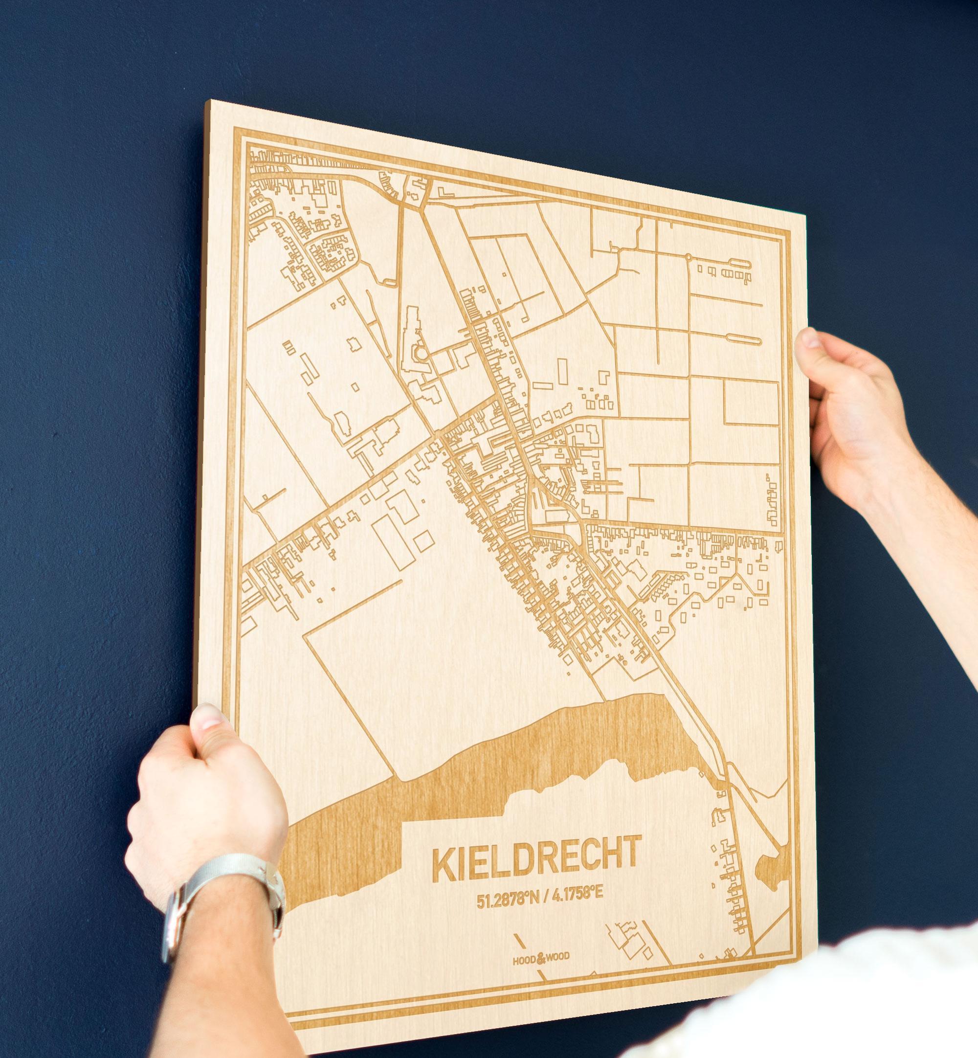 Een man hangt de houten plattegrond Kieldrecht aan zijn blauwe muur ter decoratie. Je ziet alleen zijn handen de kaart van deze opvallende in Oost-Vlaanderen  vasthouden.