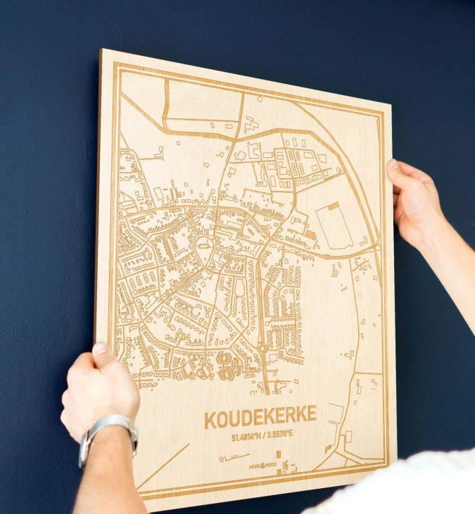 Een man hangt de houten plattegrond Koudekerke aan zijn blauwe muur ter decoratie. Je ziet alleen zijn handen de kaart van deze opvallende in Zeeland vasthouden.