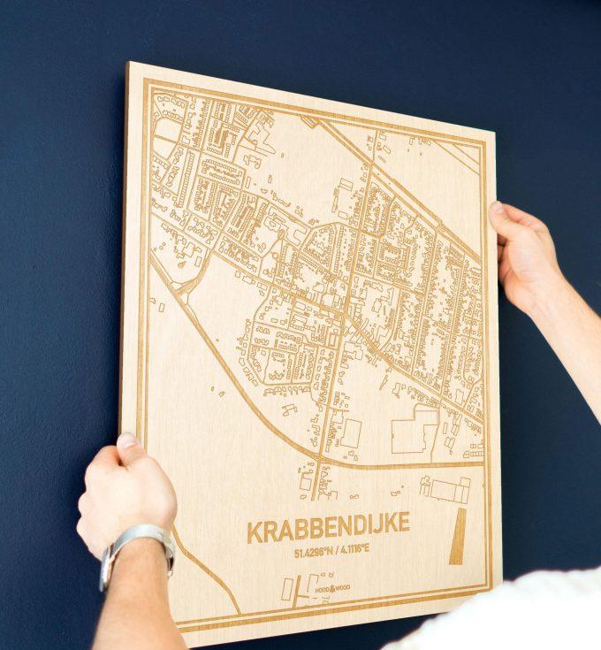 Een man hangt de houten plattegrond Krabbendijke aan zijn blauwe muur ter decoratie. Je ziet alleen zijn handen de kaart van deze originele in Zeeland vasthouden.