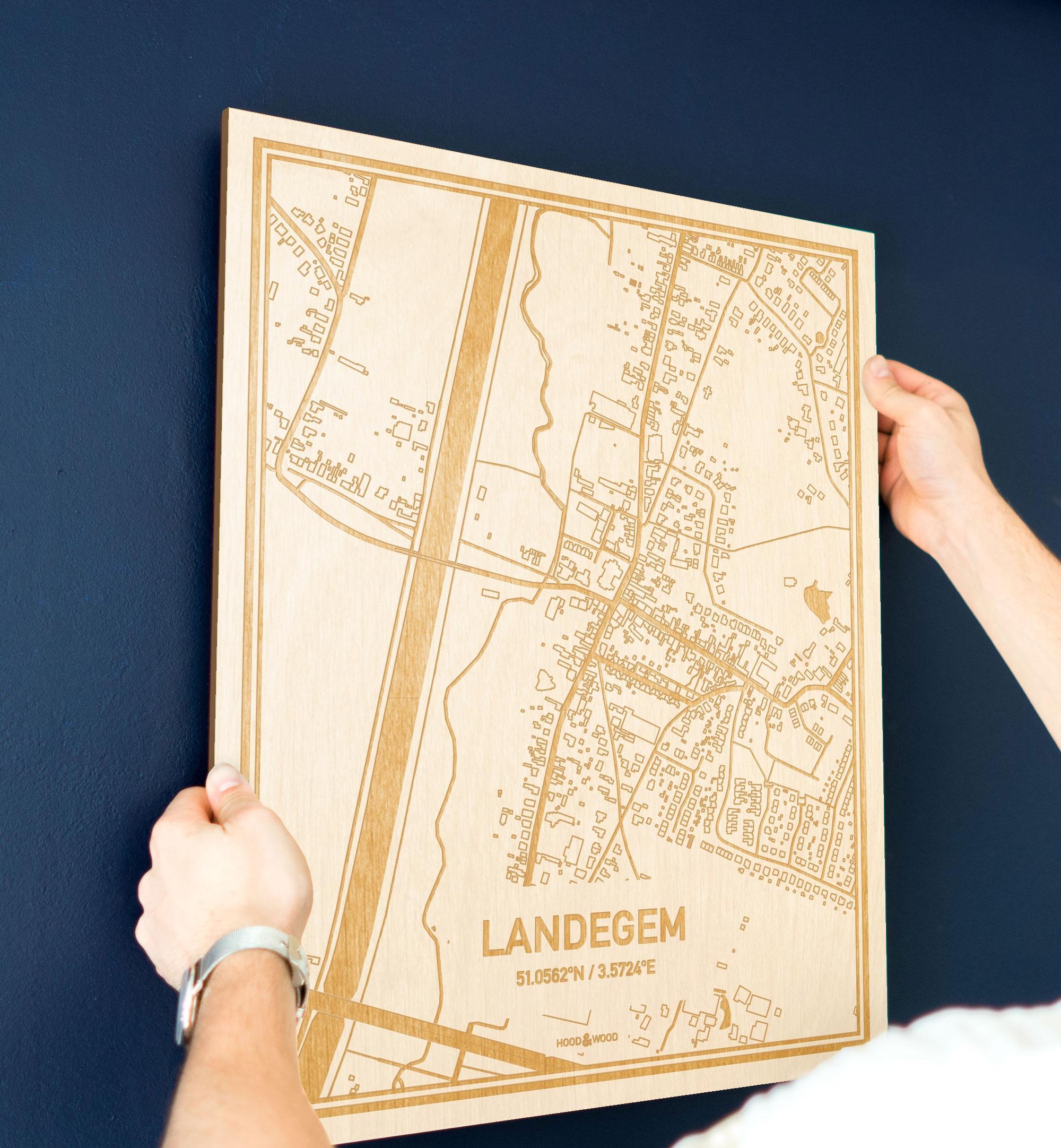 Een man hangt de houten plattegrond Landegem aan zijn blauwe muur ter decoratie. Je ziet alleen zijn handen de kaart van deze moderne in Oost-Vlaanderen  vasthouden.