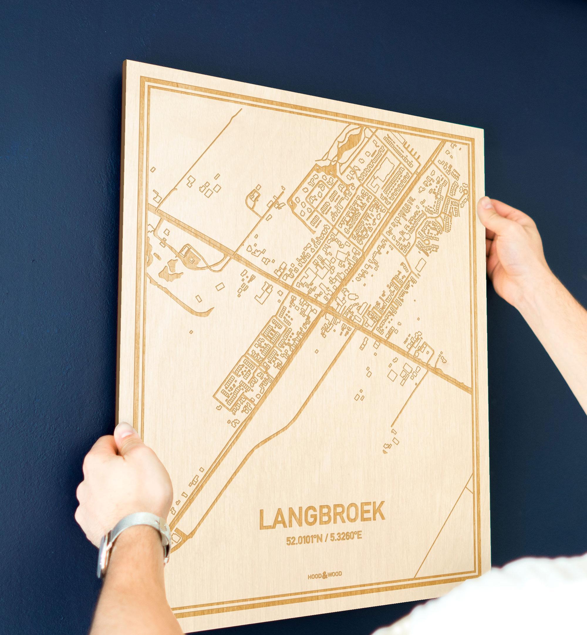 Een man hangt de houten plattegrond Langbroek aan zijn blauwe muur ter decoratie. Je ziet alleen zijn handen de kaart van deze speciale in Utrecht vasthouden.