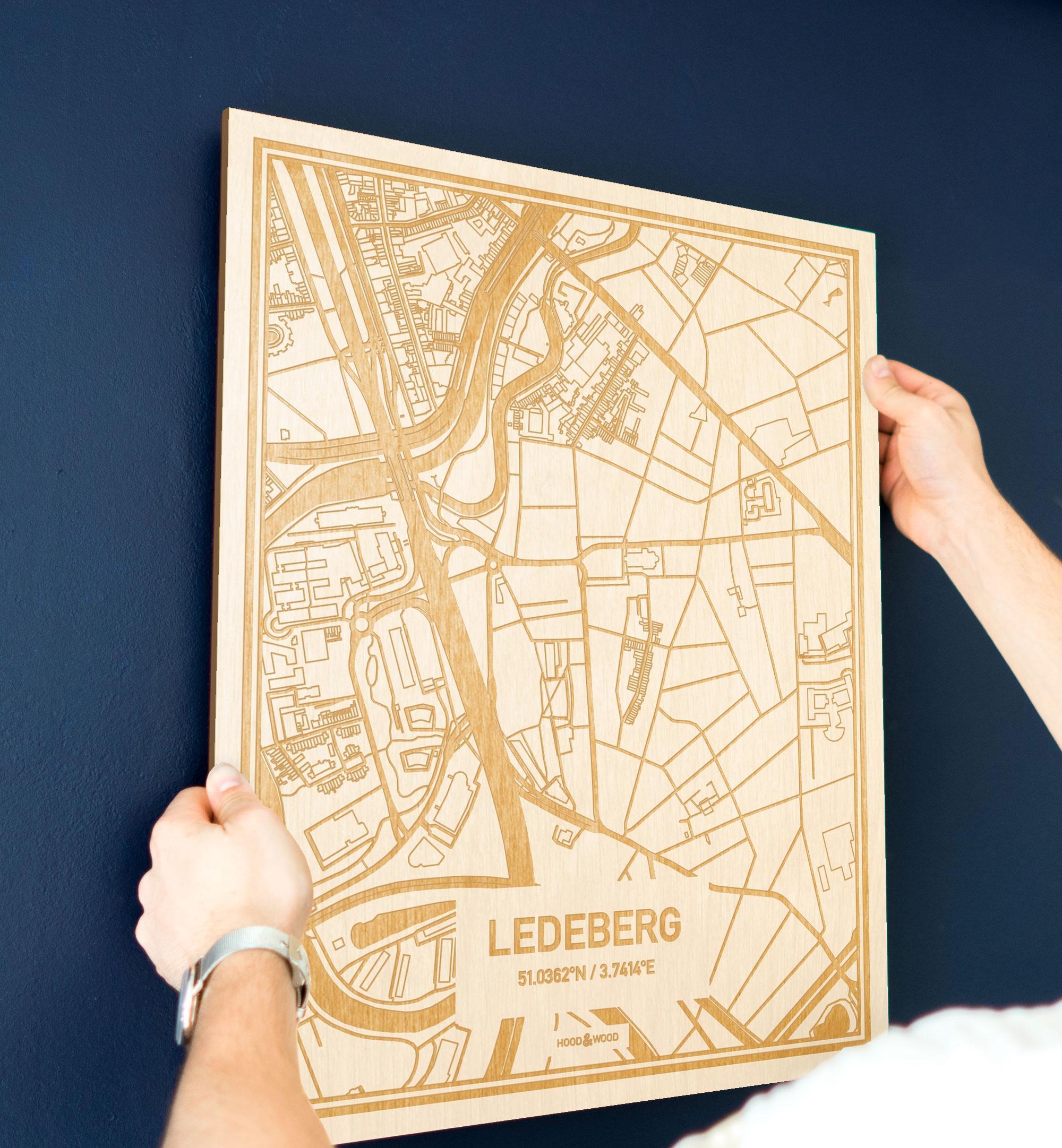 Een man hangt de houten plattegrond Ledeberg aan zijn blauwe muur ter decoratie. Je ziet alleen zijn handen de kaart van deze originele in Oost-Vlaanderen  vasthouden.
