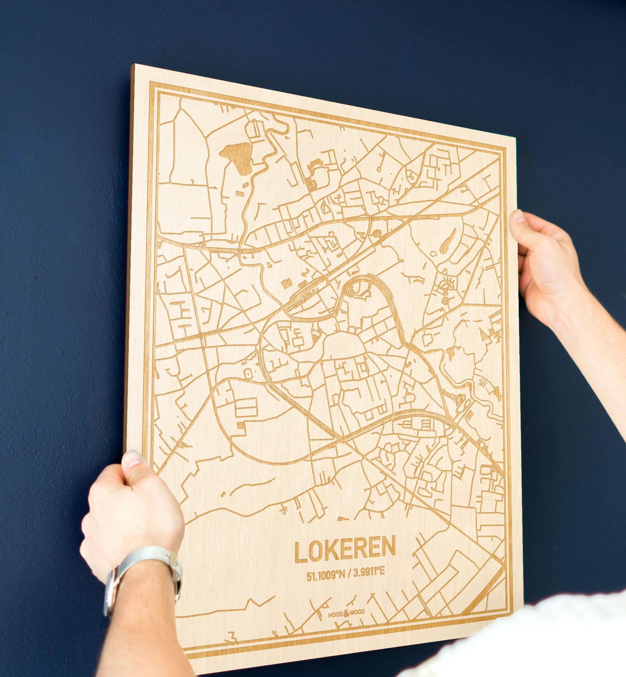 Een man hangt de houten plattegrond Lokeren aan zijn blauwe muur ter decoratie. Je ziet alleen zijn handen de kaart van deze moderne in Oost-Vlaanderen  vasthouden.