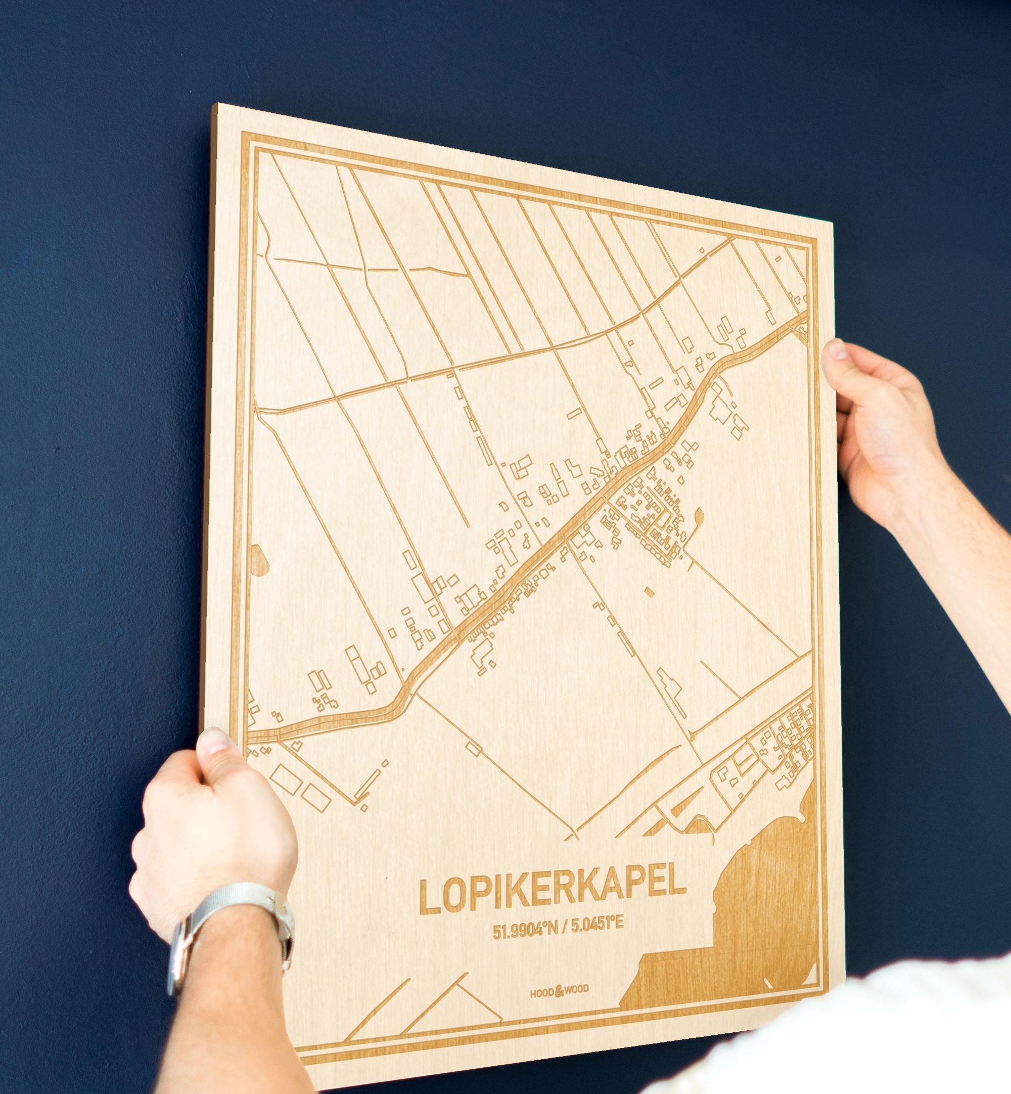 Een man hangt de houten plattegrond Lopikerkapel aan zijn blauwe muur ter decoratie. Je ziet alleen zijn handen de kaart van deze prachtige in Utrecht vasthouden.