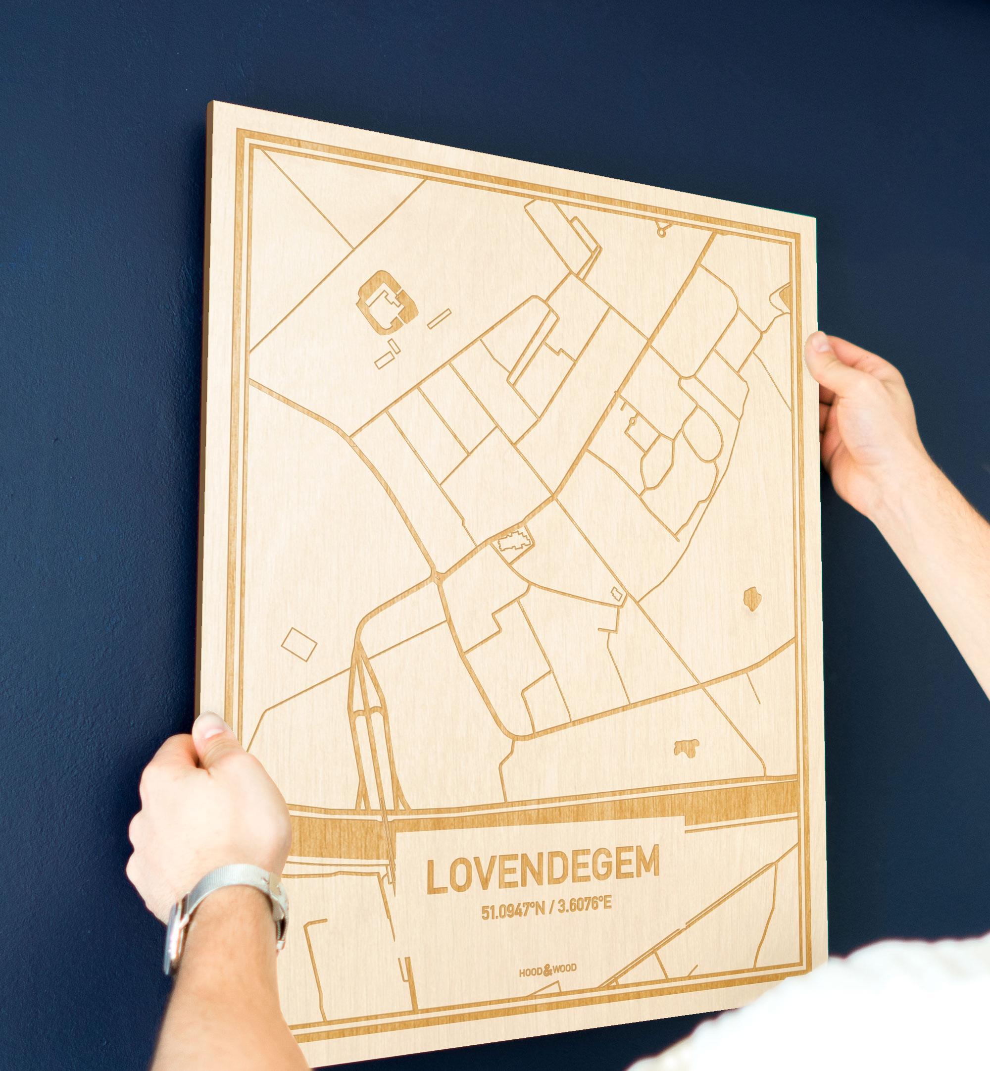 Een man hangt de houten plattegrond Lovendegem aan zijn blauwe muur ter decoratie. Je ziet alleen zijn handen de kaart van deze originele in Oost-Vlaanderen  vasthouden.