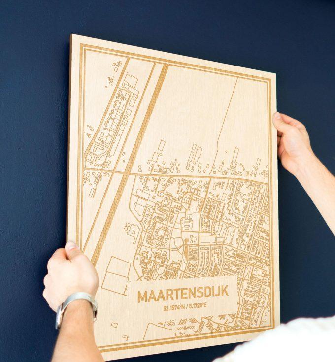 Een man hangt de houten plattegrond Maartensdijk aan zijn blauwe muur ter decoratie. Je ziet alleen zijn handen de kaart van deze opvallende in Utrecht vasthouden.