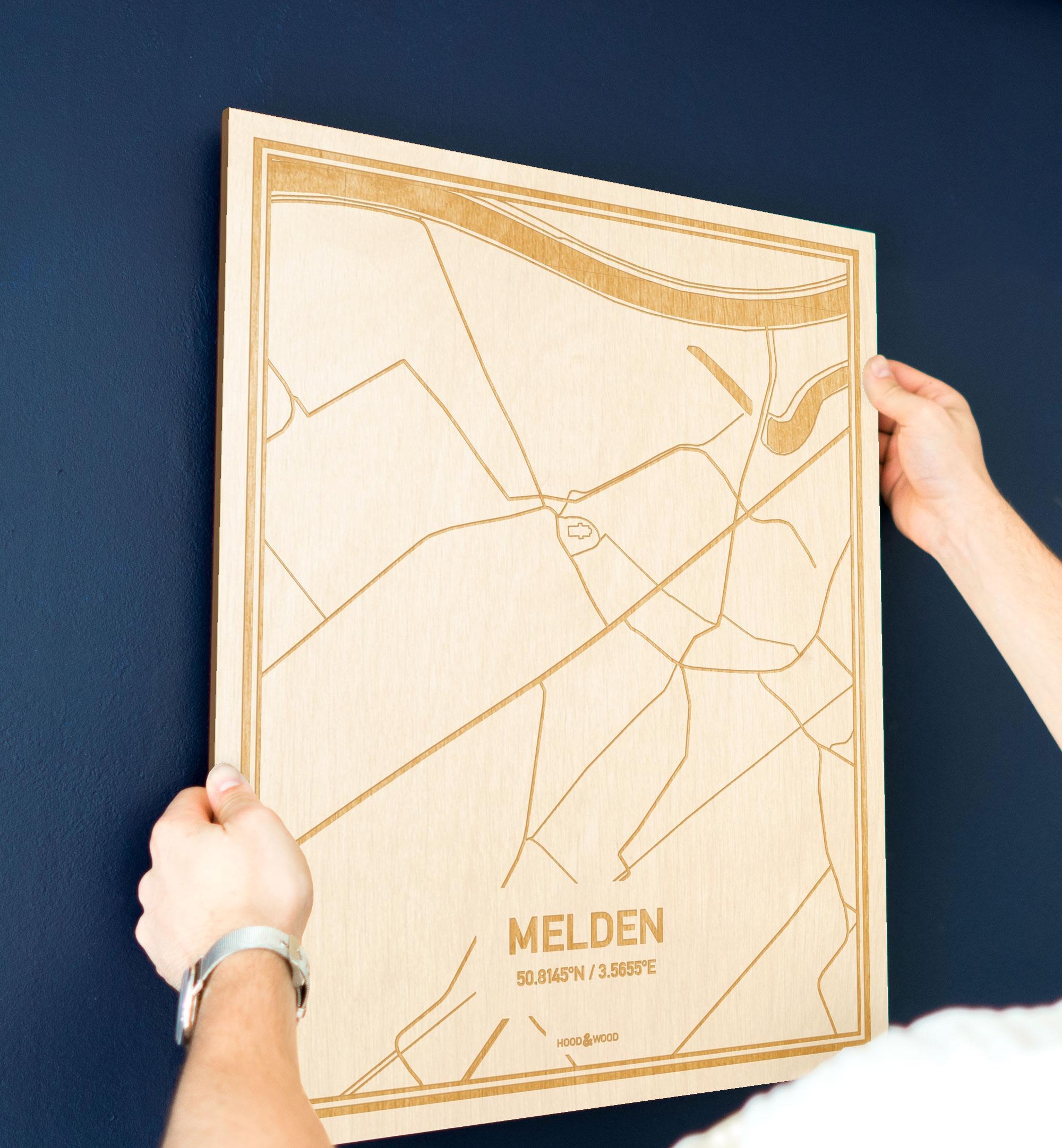 Een man hangt de houten plattegrond Melden aan zijn blauwe muur ter decoratie. Je ziet alleen zijn handen de kaart van deze unieke in Oost-Vlaanderen  vasthouden.