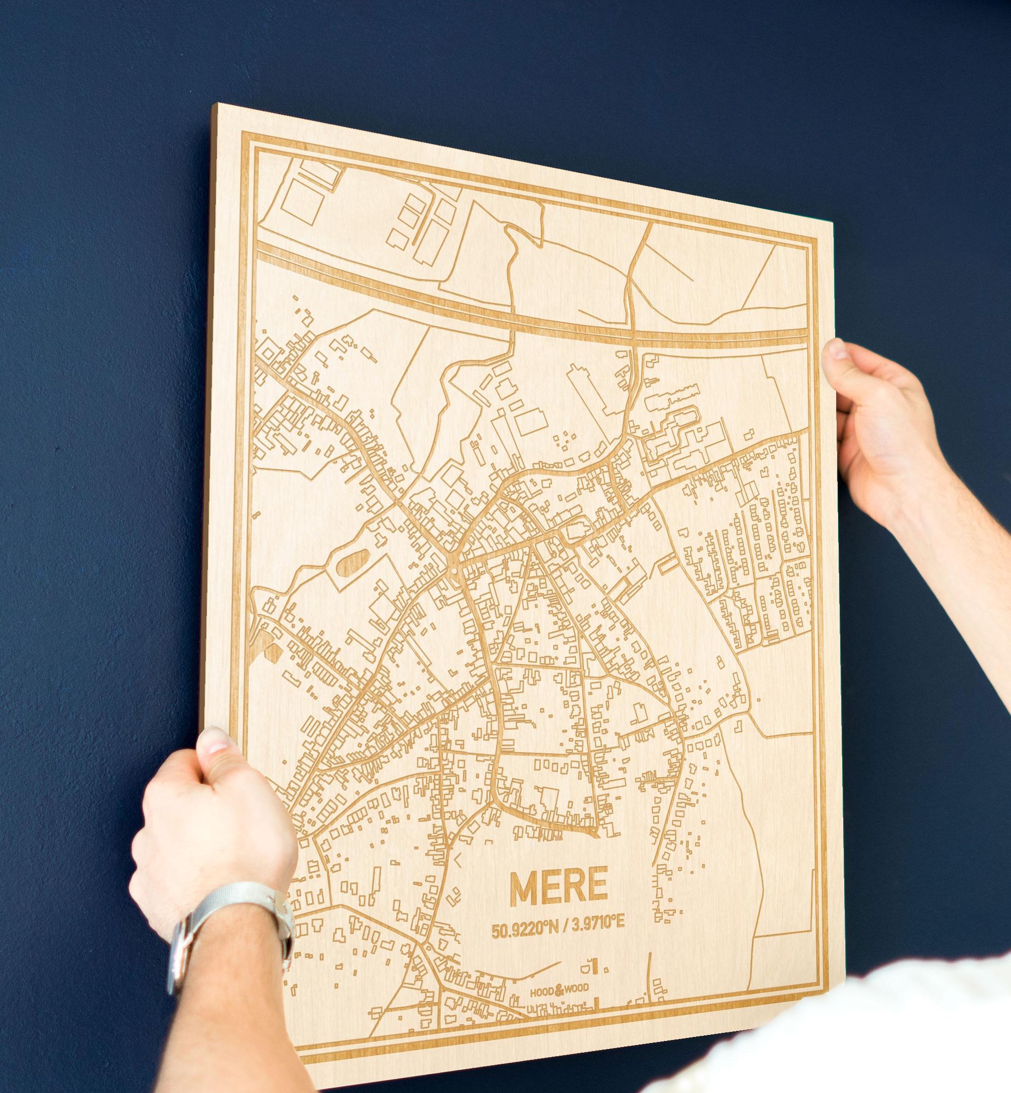 Een man hangt de houten plattegrond Mere aan zijn blauwe muur ter decoratie. Je ziet alleen zijn handen de kaart van deze moderne in Oost-Vlaanderen  vasthouden.