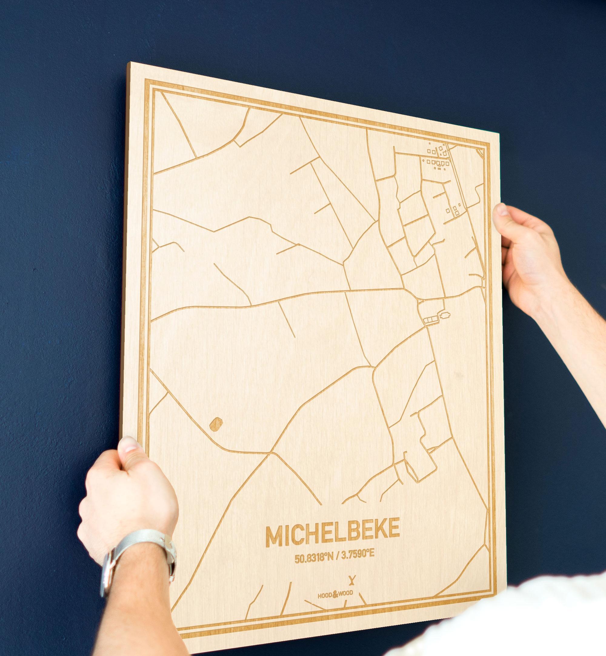 Een man hangt de houten plattegrond Michelbeke aan zijn blauwe muur ter decoratie. Je ziet alleen zijn handen de kaart van deze originele in Oost-Vlaanderen  vasthouden.