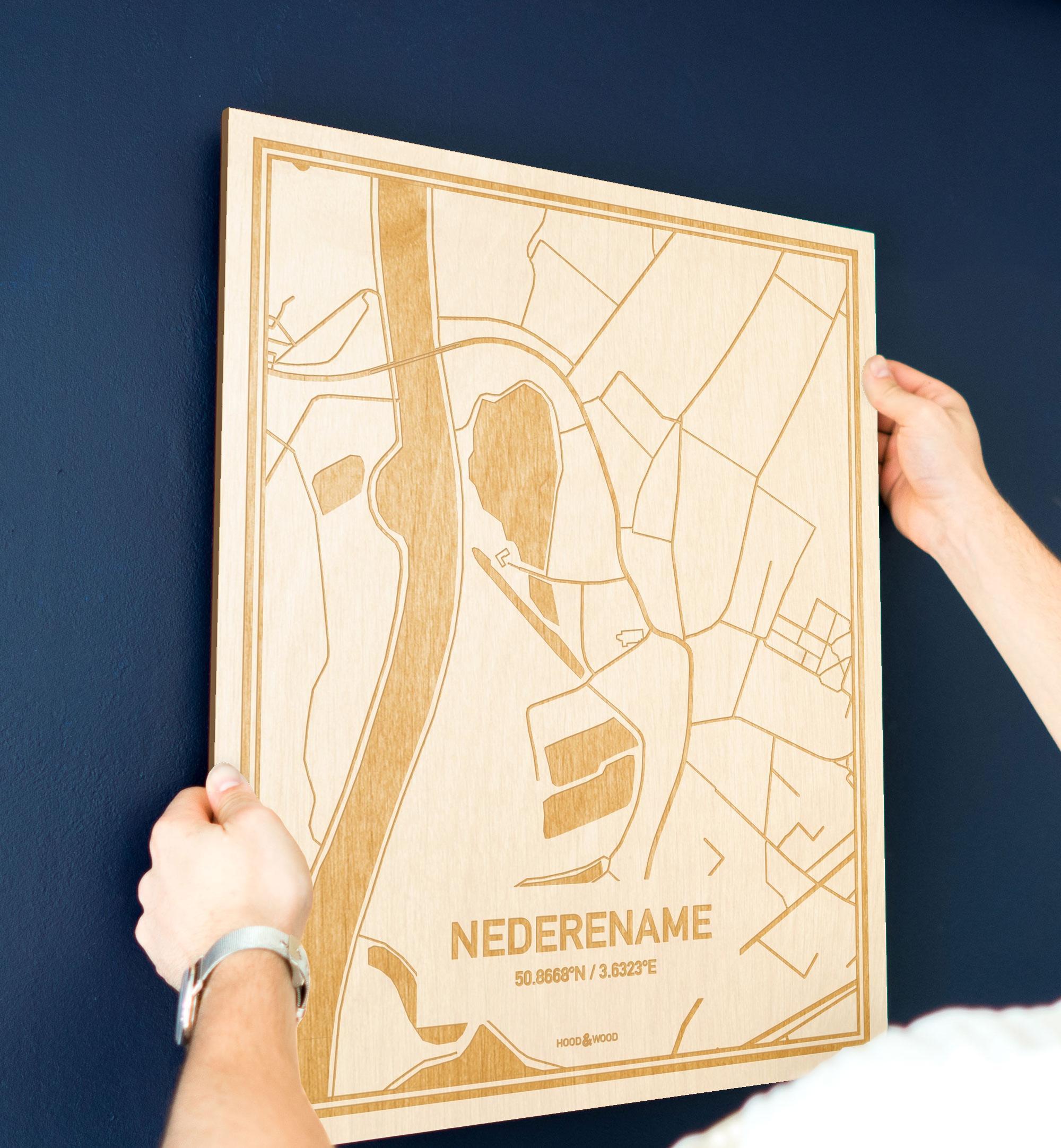 Een man hangt de houten plattegrond Nederename aan zijn blauwe muur ter decoratie. Je ziet alleen zijn handen de kaart van deze moderne in Oost-Vlaanderen  vasthouden.