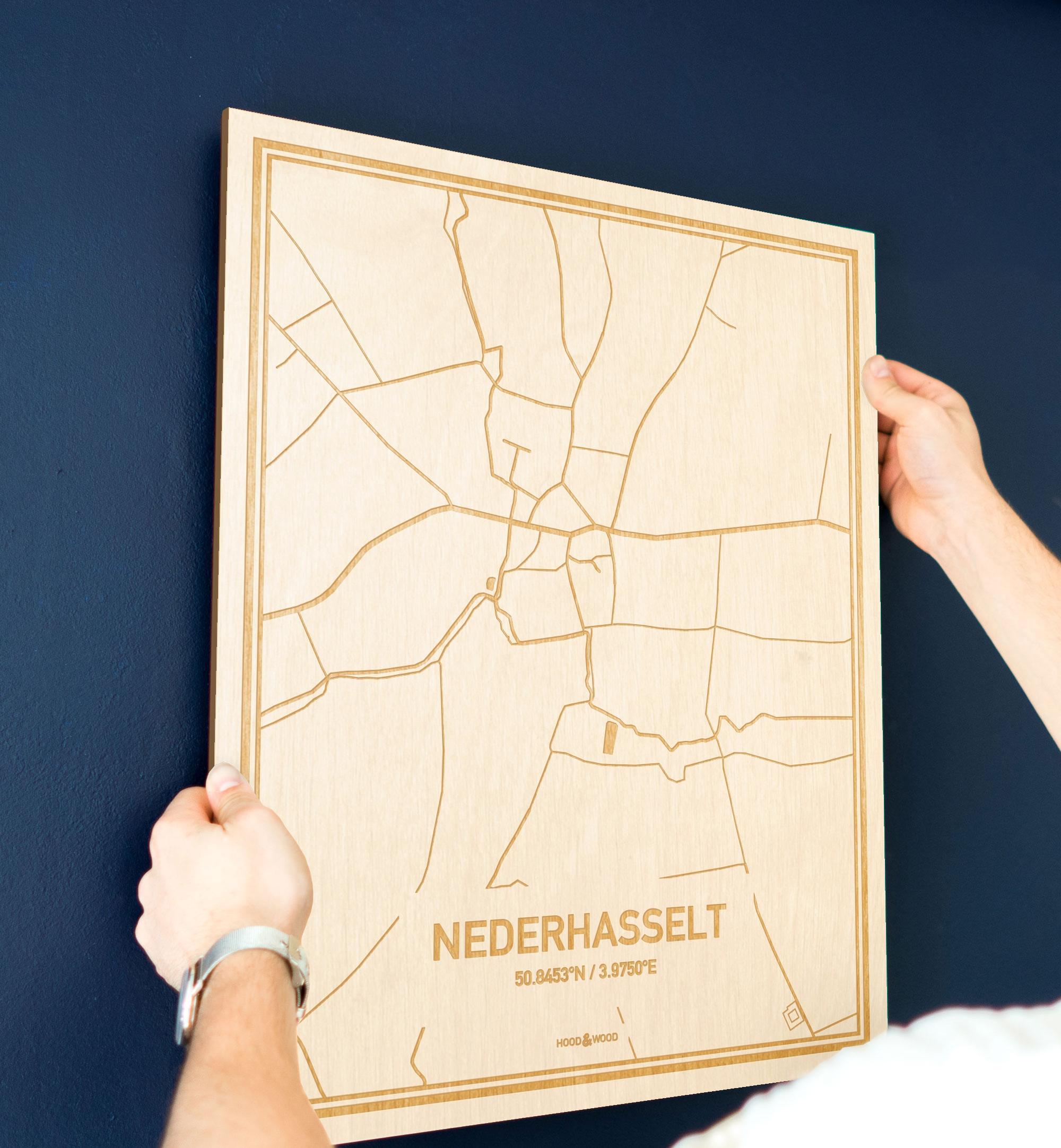 Een man hangt de houten plattegrond Nederhasselt aan zijn blauwe muur ter decoratie. Je ziet alleen zijn handen de kaart van deze speciale in Oost-Vlaanderen  vasthouden.