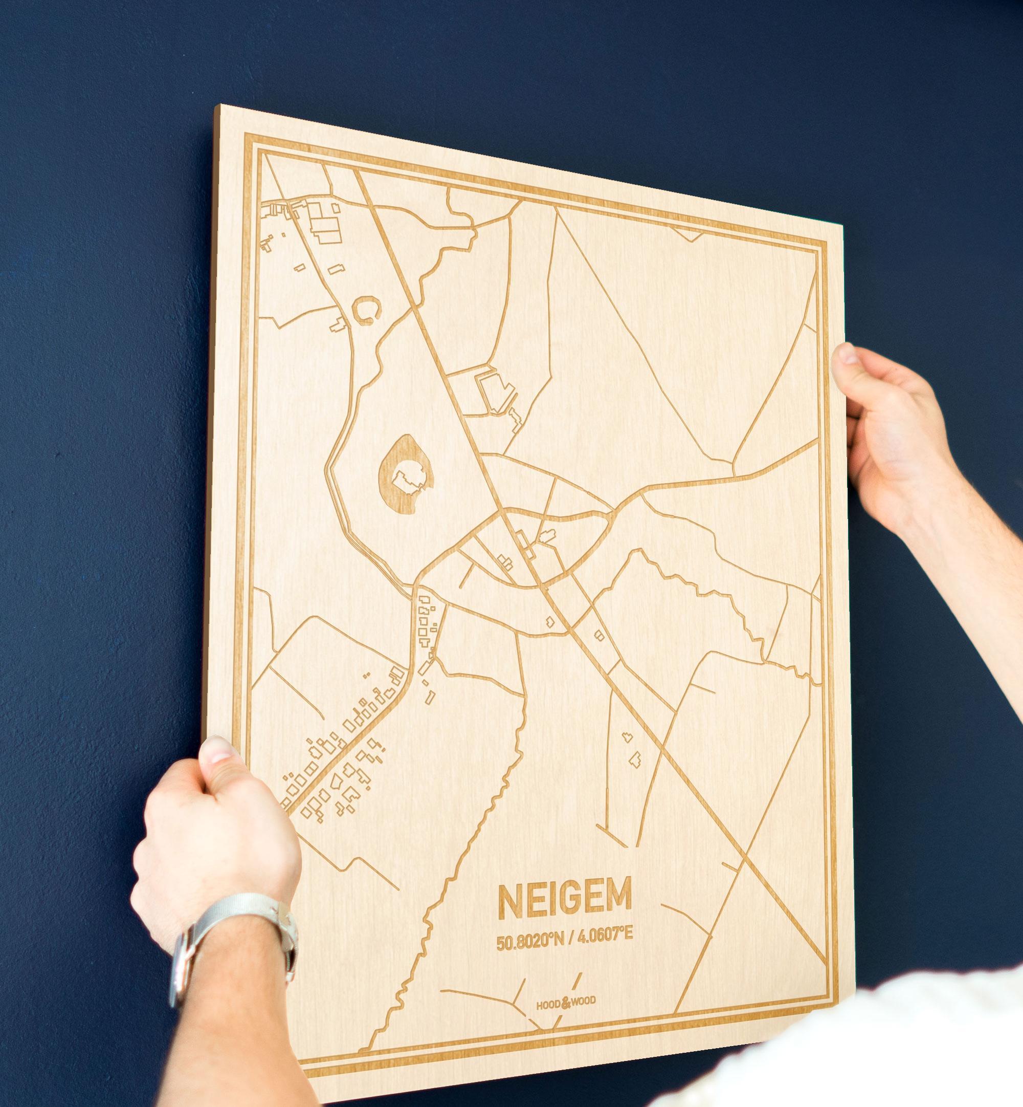 Een man hangt de houten plattegrond Neigem aan zijn blauwe muur ter decoratie. Je ziet alleen zijn handen de kaart van deze unieke in Oost-Vlaanderen  vasthouden.