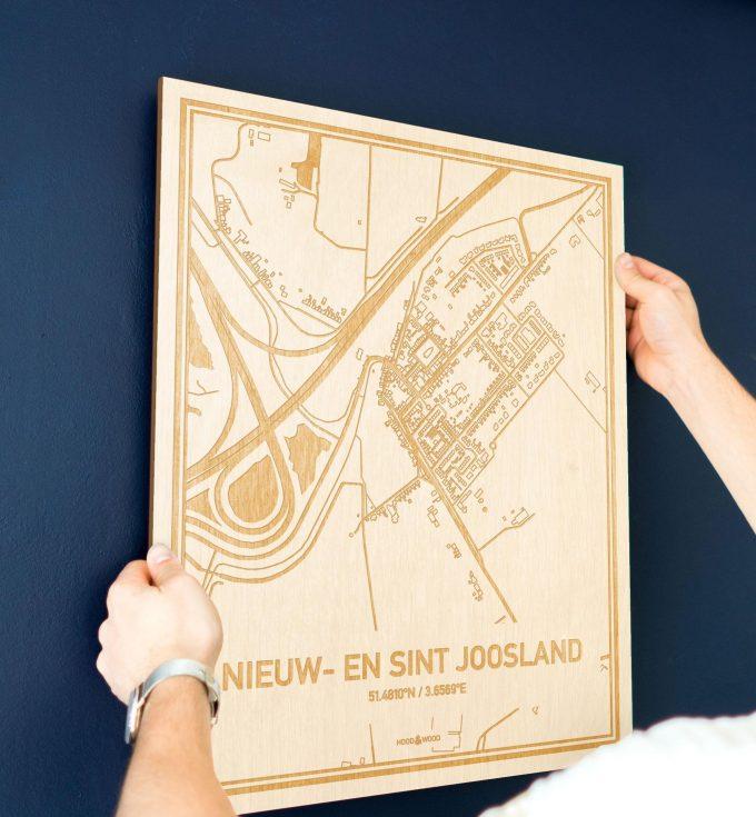 Een man hangt de houten plattegrond Nieuw- en Sint Joosland aan zijn blauwe muur ter decoratie. Je ziet alleen zijn handen de kaart van deze schitterende in Zeeland vasthouden.
