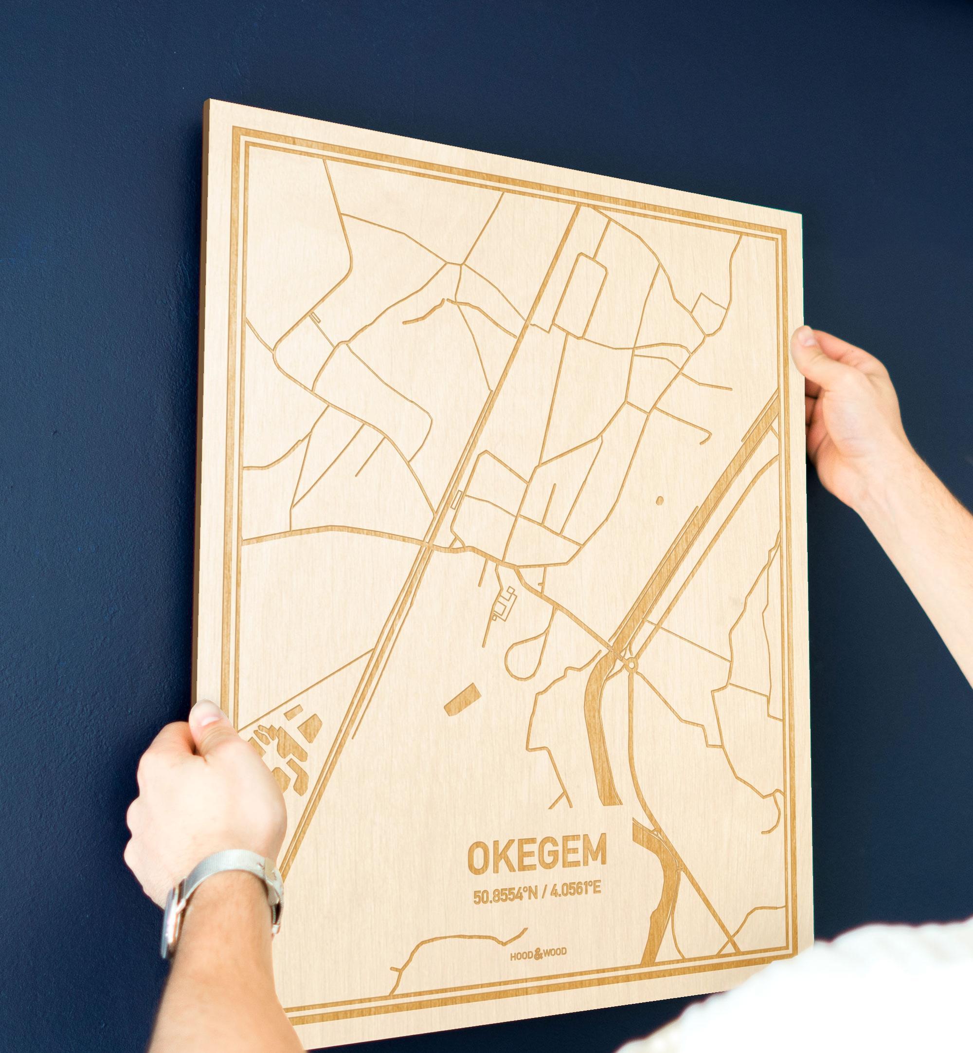 Een man hangt de houten plattegrond Okegem aan zijn blauwe muur ter decoratie. Je ziet alleen zijn handen de kaart van deze bijzondere in Oost-Vlaanderen  vasthouden.