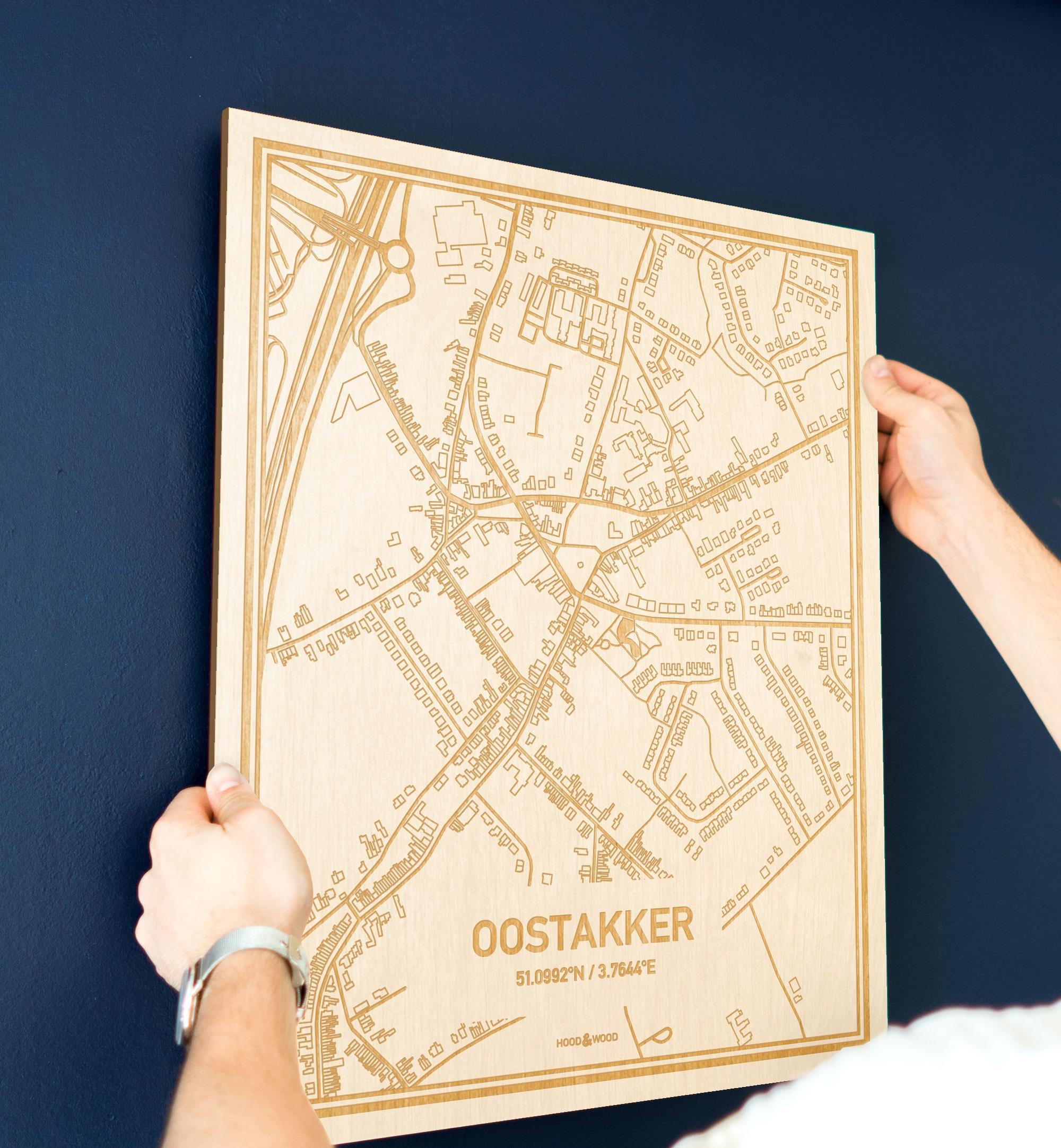 Een man hangt de houten plattegrond Oostakker aan zijn blauwe muur ter decoratie. Je ziet alleen zijn handen de kaart van deze bijzondere in Oost-Vlaanderen  vasthouden.