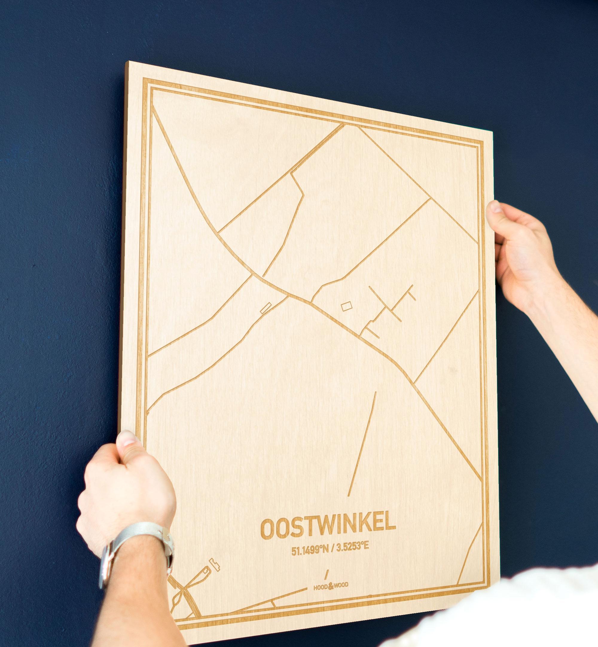 Een man hangt de houten plattegrond Oostwinkel aan zijn blauwe muur ter decoratie. Je ziet alleen zijn handen de kaart van deze opvallende in Oost-Vlaanderen  vasthouden.