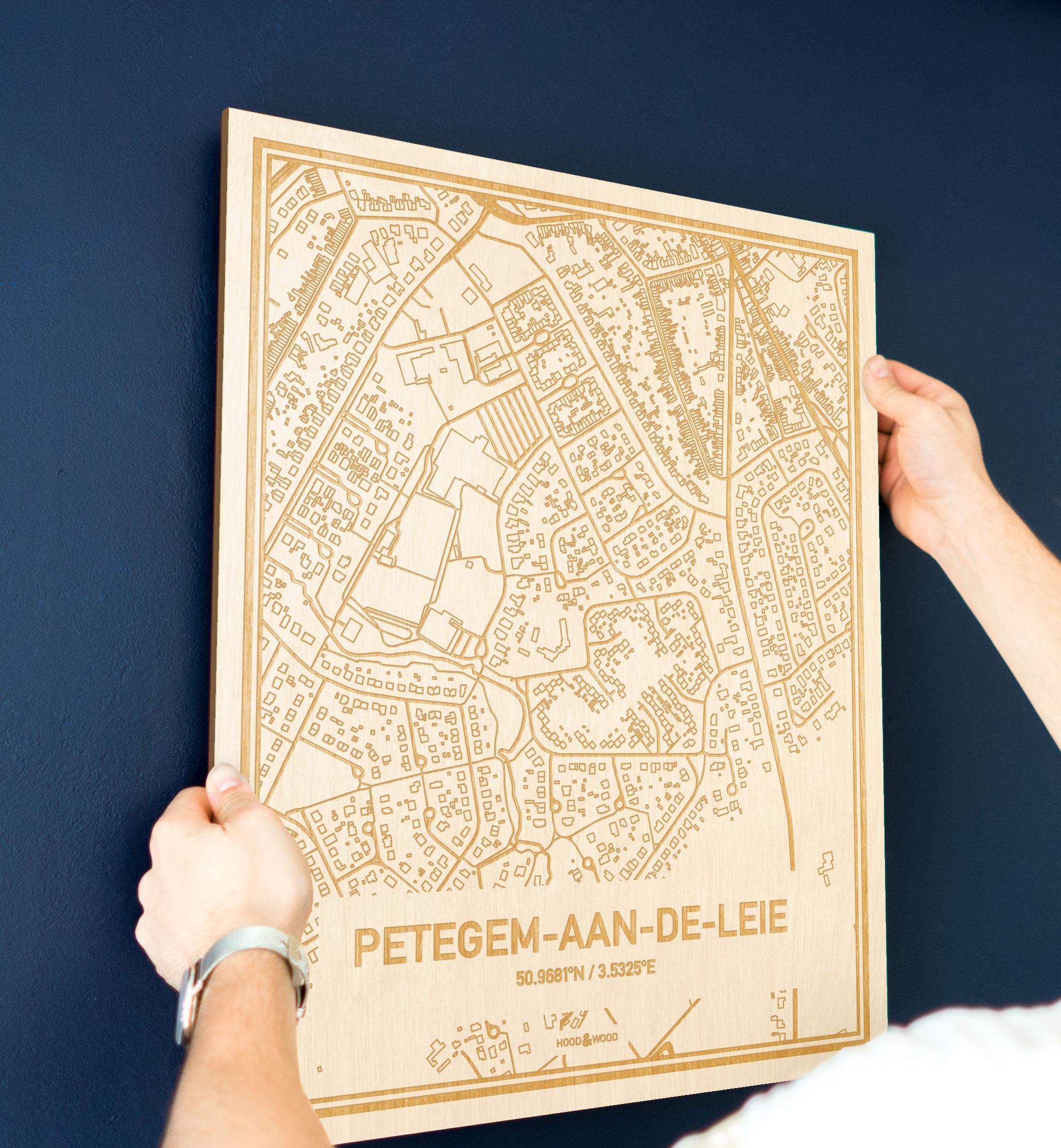 Een man hangt de houten plattegrond Petegem-Aan-De-Leie aan zijn blauwe muur ter decoratie. Je ziet alleen zijn handen de kaart van deze bijzondere in Oost-Vlaanderen  vasthouden.