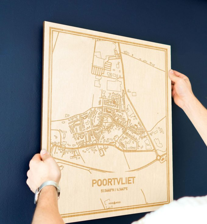 Een man hangt de houten plattegrond Poortvliet aan zijn blauwe muur ter decoratie. Je ziet alleen zijn handen de kaart van deze schitterende in Zeeland vasthouden.