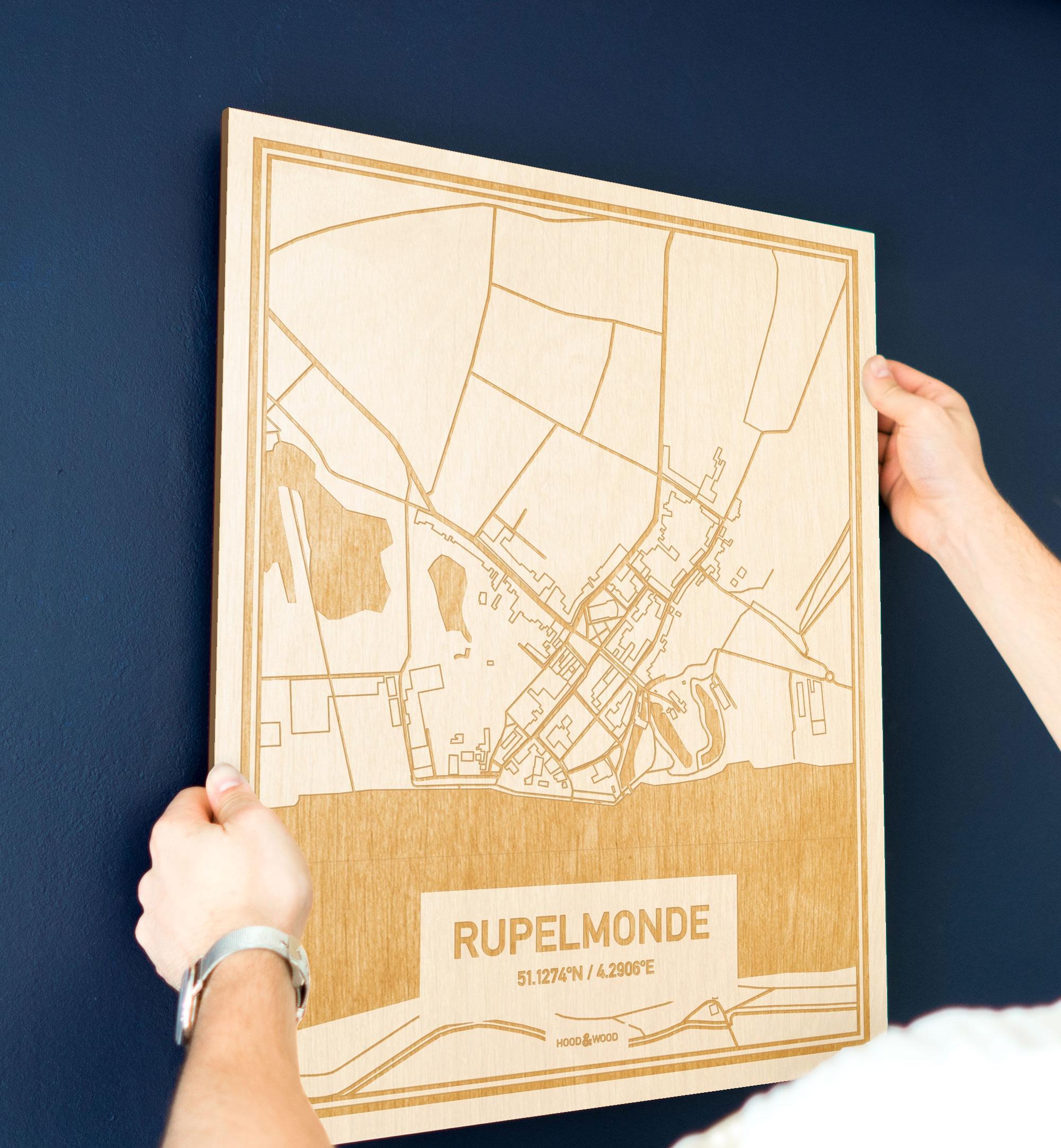 Een man hangt de houten plattegrond Rupelmonde aan zijn blauwe muur ter decoratie. Je ziet alleen zijn handen de kaart van deze moderne in Oost-Vlaanderen  vasthouden.