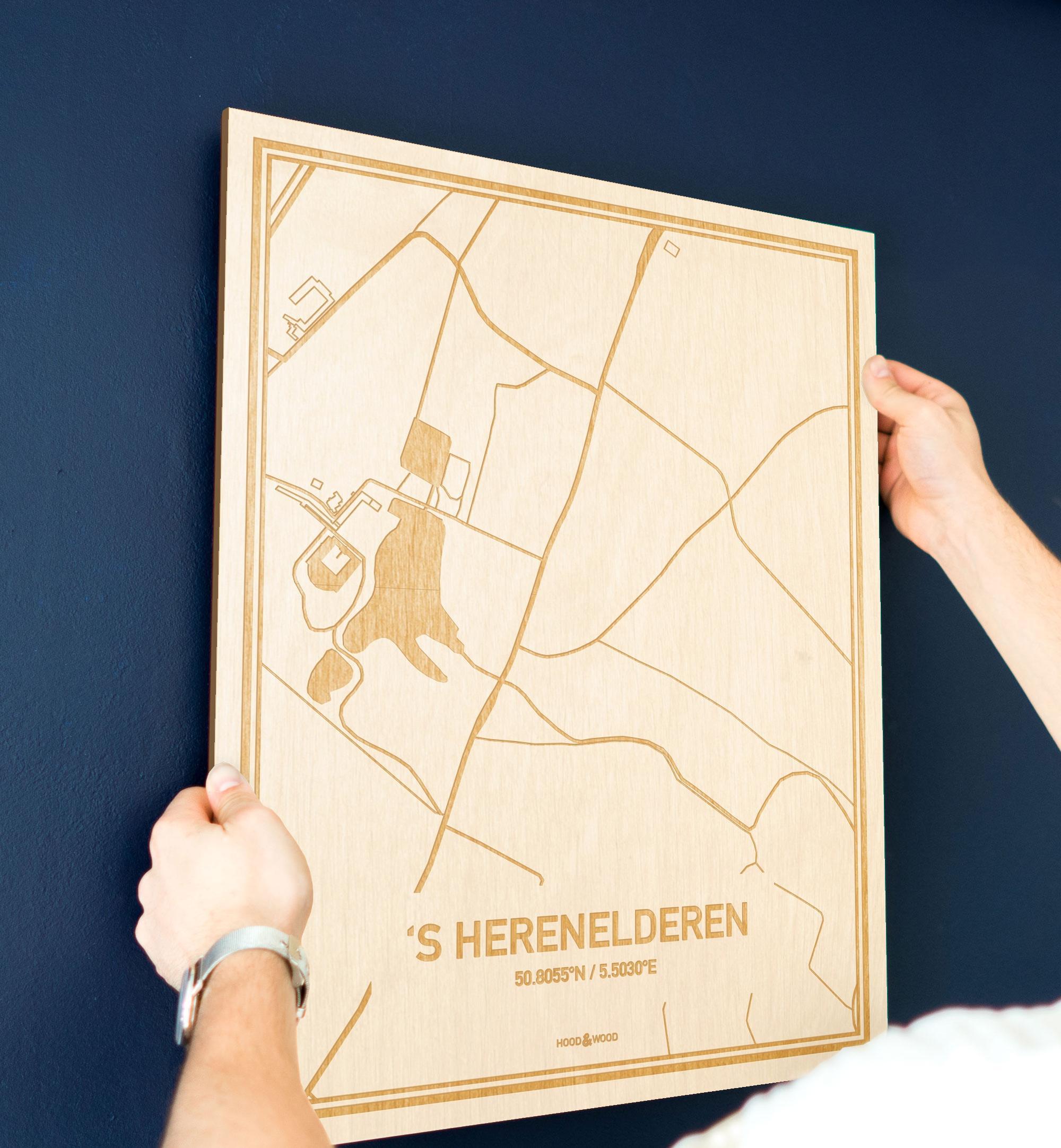 Een man hangt de houten plattegrond 'S Herenelderen aan zijn blauwe muur ter decoratie. Je ziet alleen zijn handen de kaart van deze unieke in Limburg vasthouden.