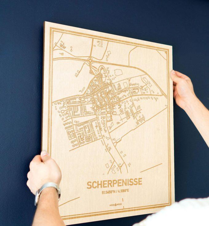 Een man hangt de houten plattegrond Scherpenisse aan zijn blauwe muur ter decoratie. Je ziet alleen zijn handen de kaart van deze verrassende in Zeeland vasthouden.