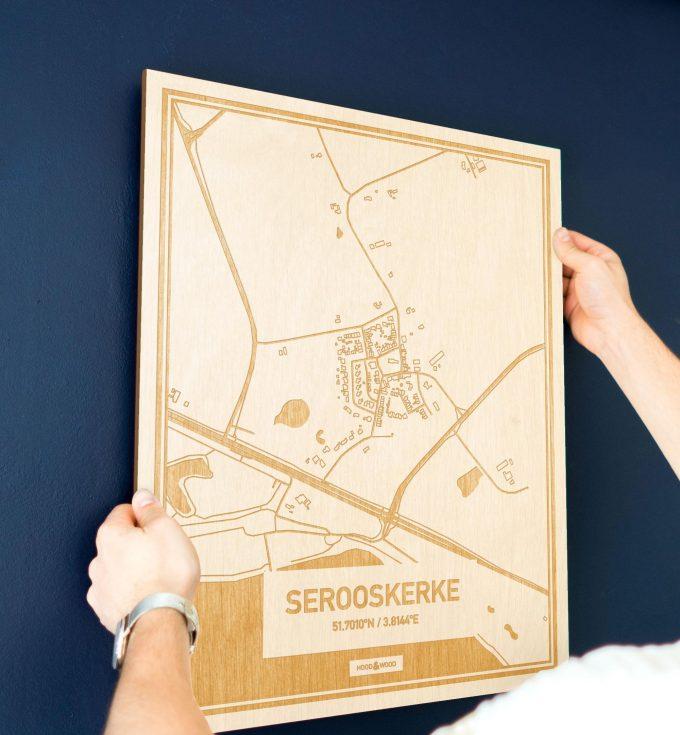 Een man hangt de houten plattegrond Serooskerke aan zijn blauwe muur ter decoratie. Je ziet alleen zijn handen de kaart van deze verrassende in Zeeland vasthouden.