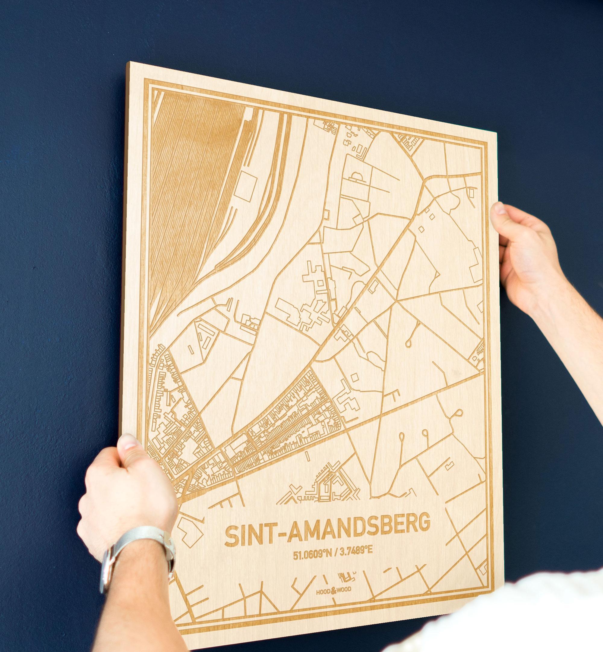 Een man hangt de houten plattegrond Sint-Amandsberg aan zijn blauwe muur ter decoratie. Je ziet alleen zijn handen de kaart van deze verrassende in Oost-Vlaanderen  vasthouden.