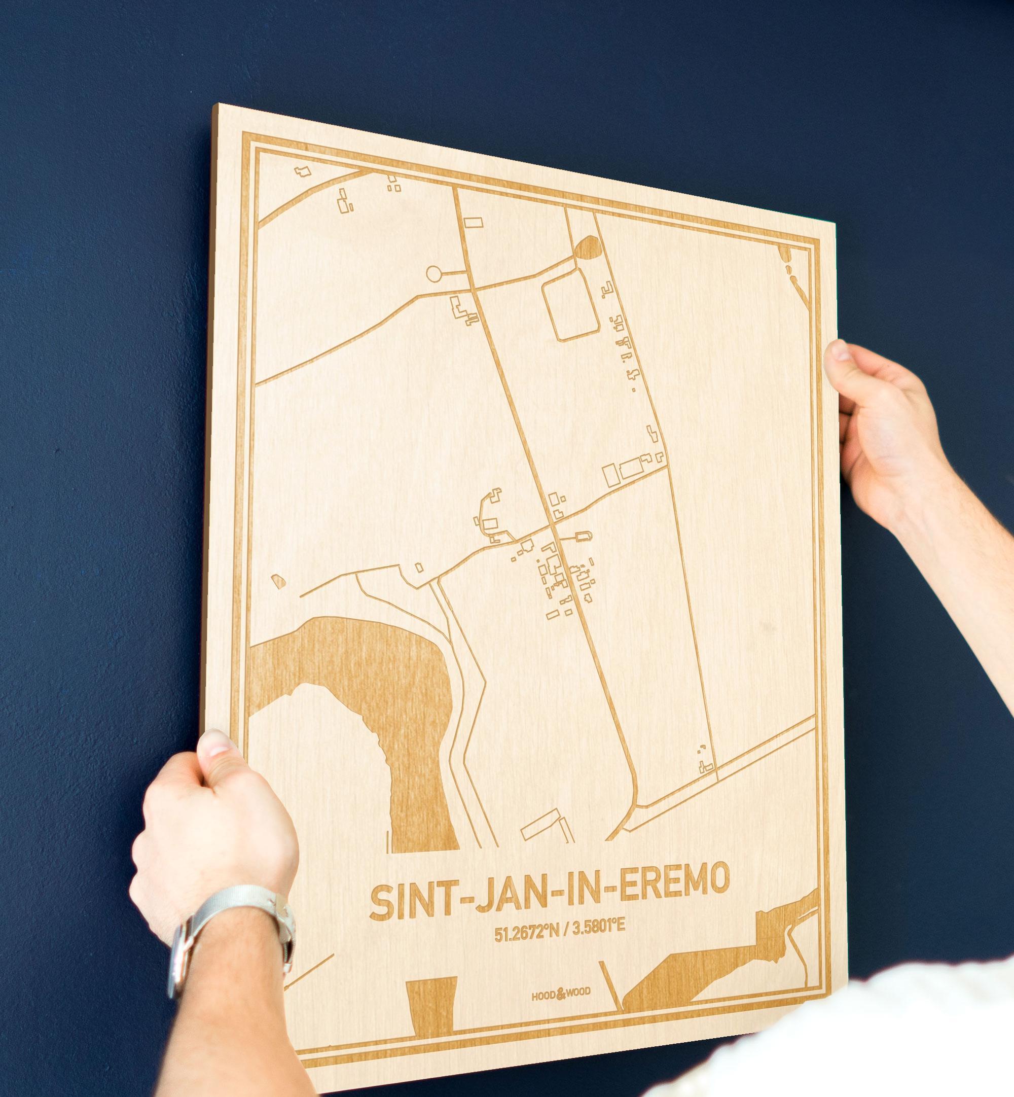 Een man hangt de houten plattegrond Sint-Jan-In-Eremo aan zijn blauwe muur ter decoratie. Je ziet alleen zijn handen de kaart van deze originele in Oost-Vlaanderen  vasthouden.