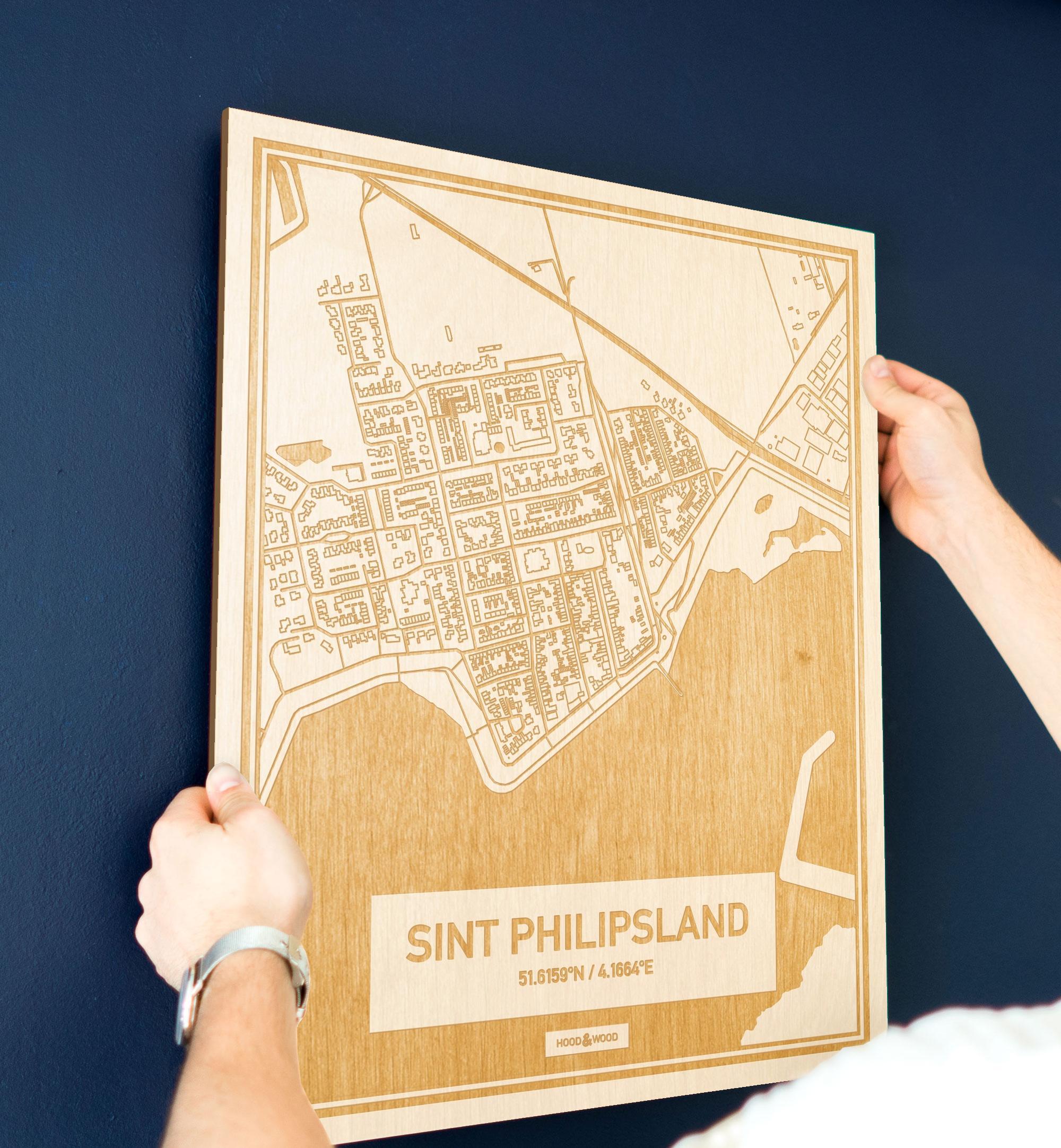 Een man hangt de houten plattegrond Sint Philipsland aan zijn blauwe muur ter decoratie. Je ziet alleen zijn handen de kaart van deze schitterende in Zeeland vasthouden.