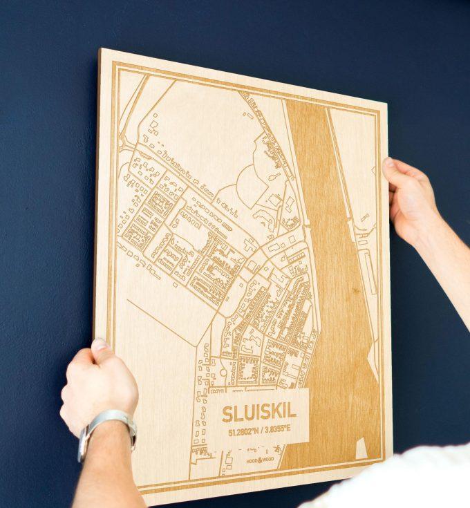 Een man hangt de houten plattegrond Sluiskil aan zijn blauwe muur ter decoratie. Je ziet alleen zijn handen de kaart van deze verrassende in Zeeland vasthouden.