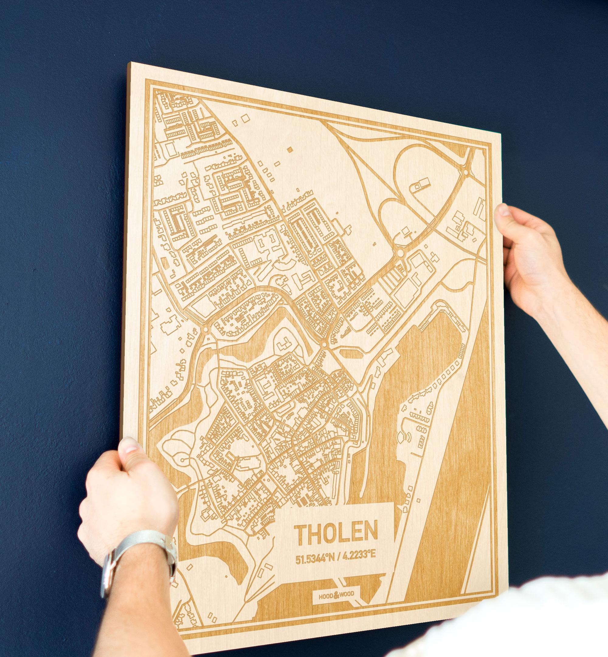 Een man hangt de houten plattegrond Tholen aan zijn blauwe muur ter decoratie. Je ziet alleen zijn handen de kaart van deze originele in Zeeland vasthouden.