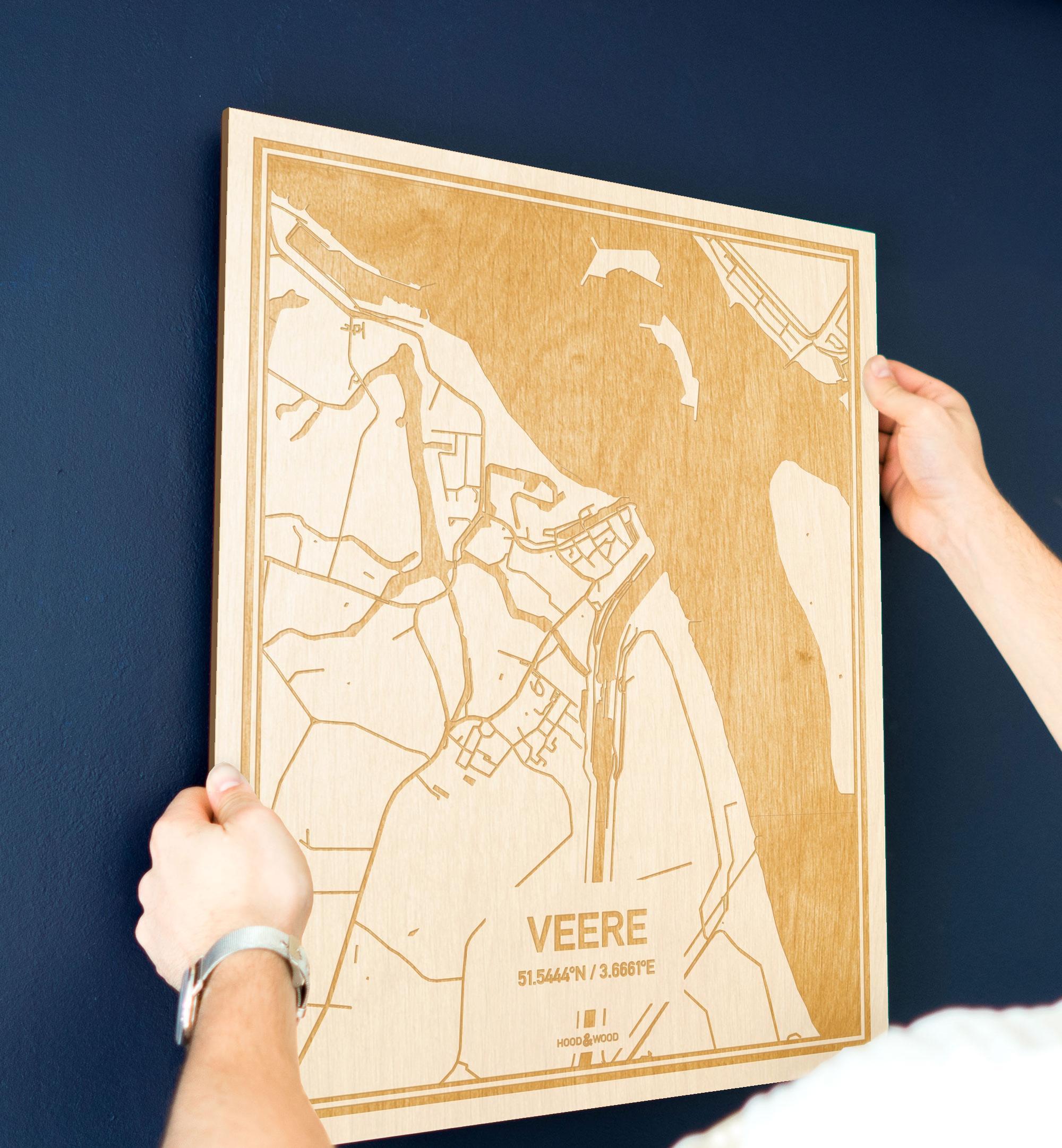 Een man hangt de houten plattegrond Veere aan zijn blauwe muur ter decoratie. Je ziet alleen zijn handen de kaart van deze prachtige in Zeeland vasthouden.